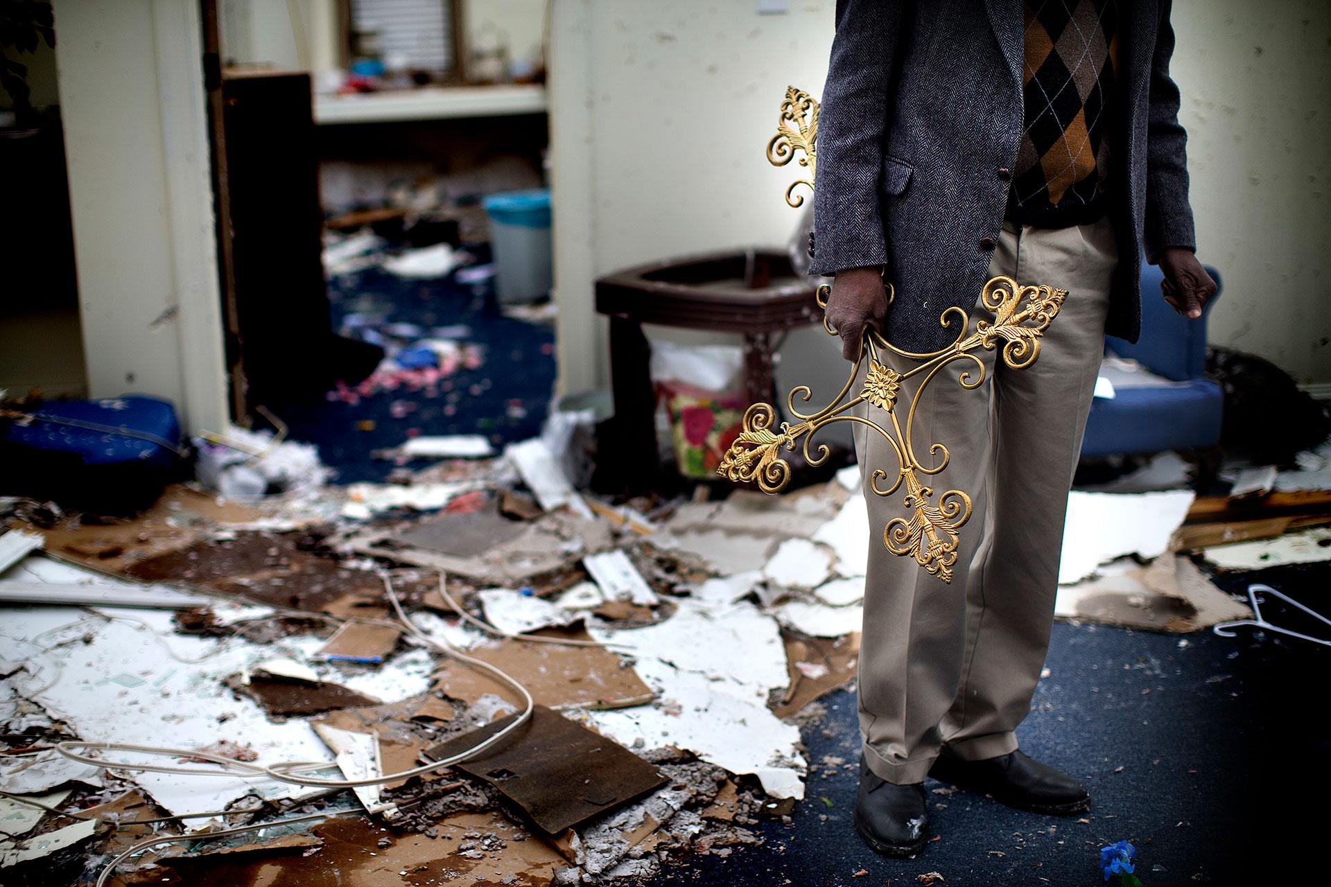 Woodard porta en su mano derecha una cruz de metal que rescató entre los escombros de su oficina