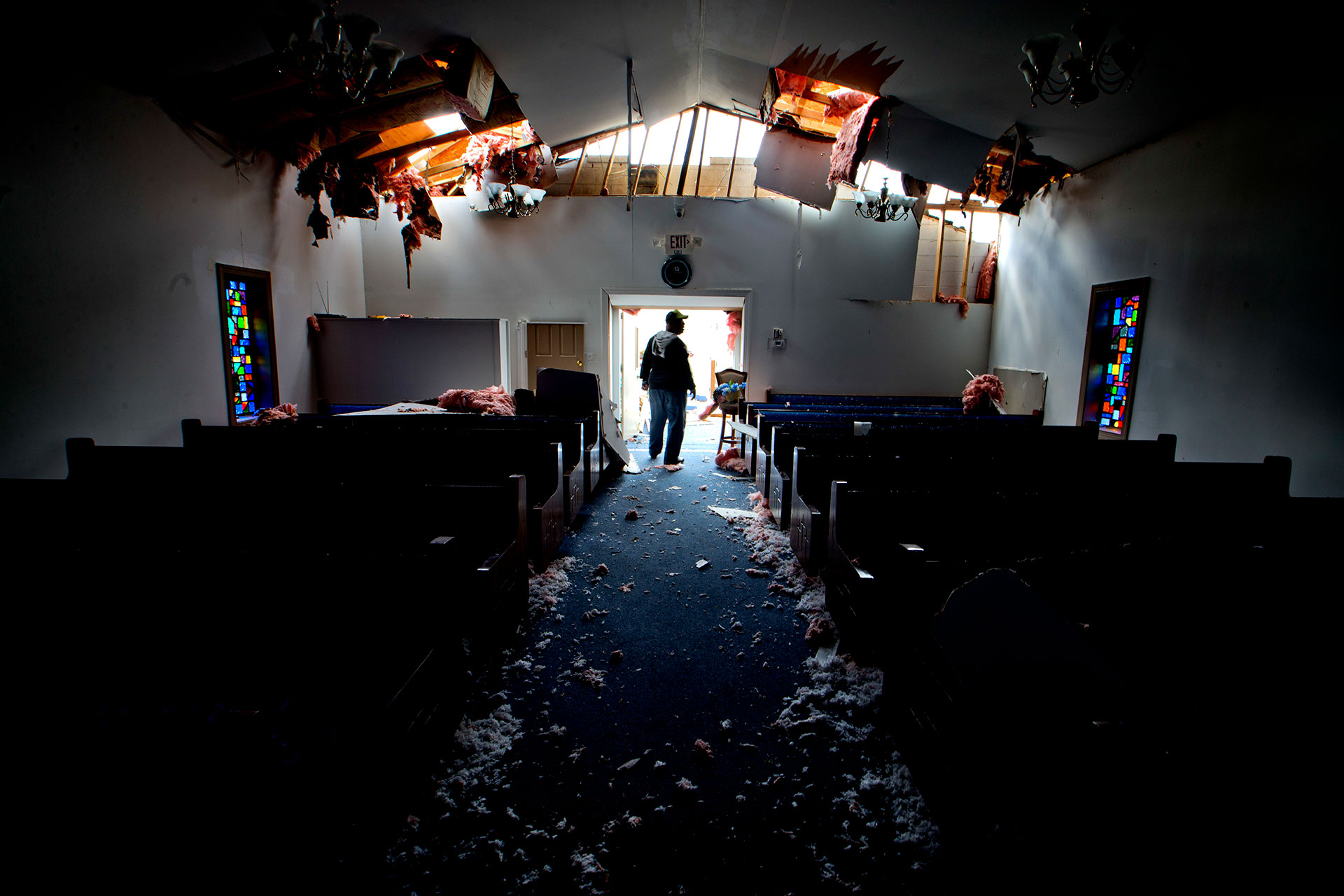 El feligrés Stratford Scott camina entre los restos de la iglesia bautista Misioneros de la Esperanza