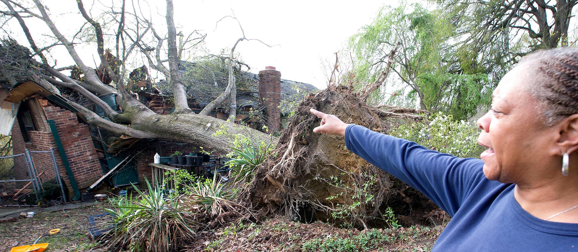 Shirl Davis muestra lo que le sucedió a la casa de su vecina el día después del tornado que afectó a la ciudaddeGreensboro, en North Carolina