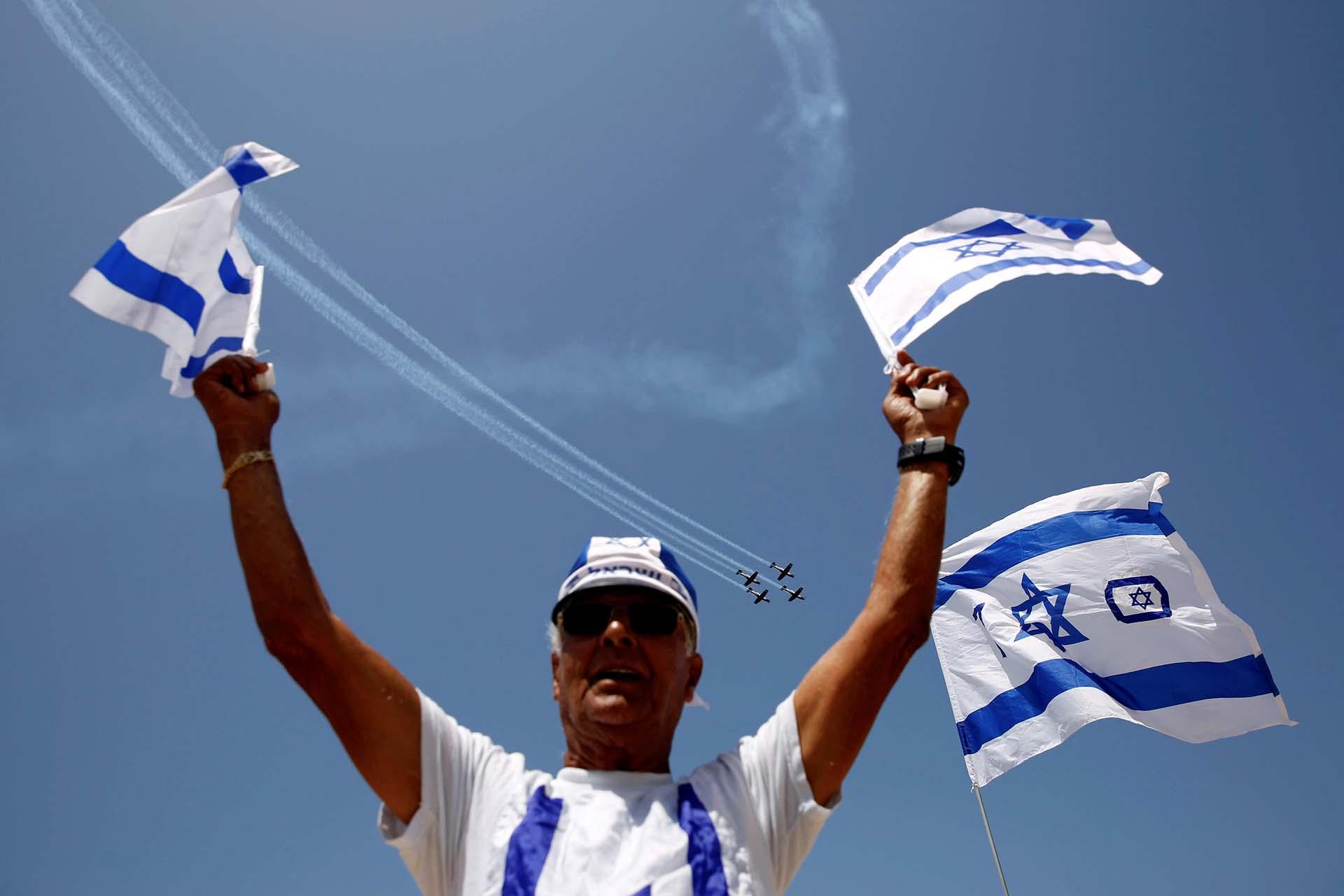 Un hombre flamea las banderas de Israel, mientras en las alturas sobrevuelan cuatro aviones militares (REUTERS/Amir Cohen)