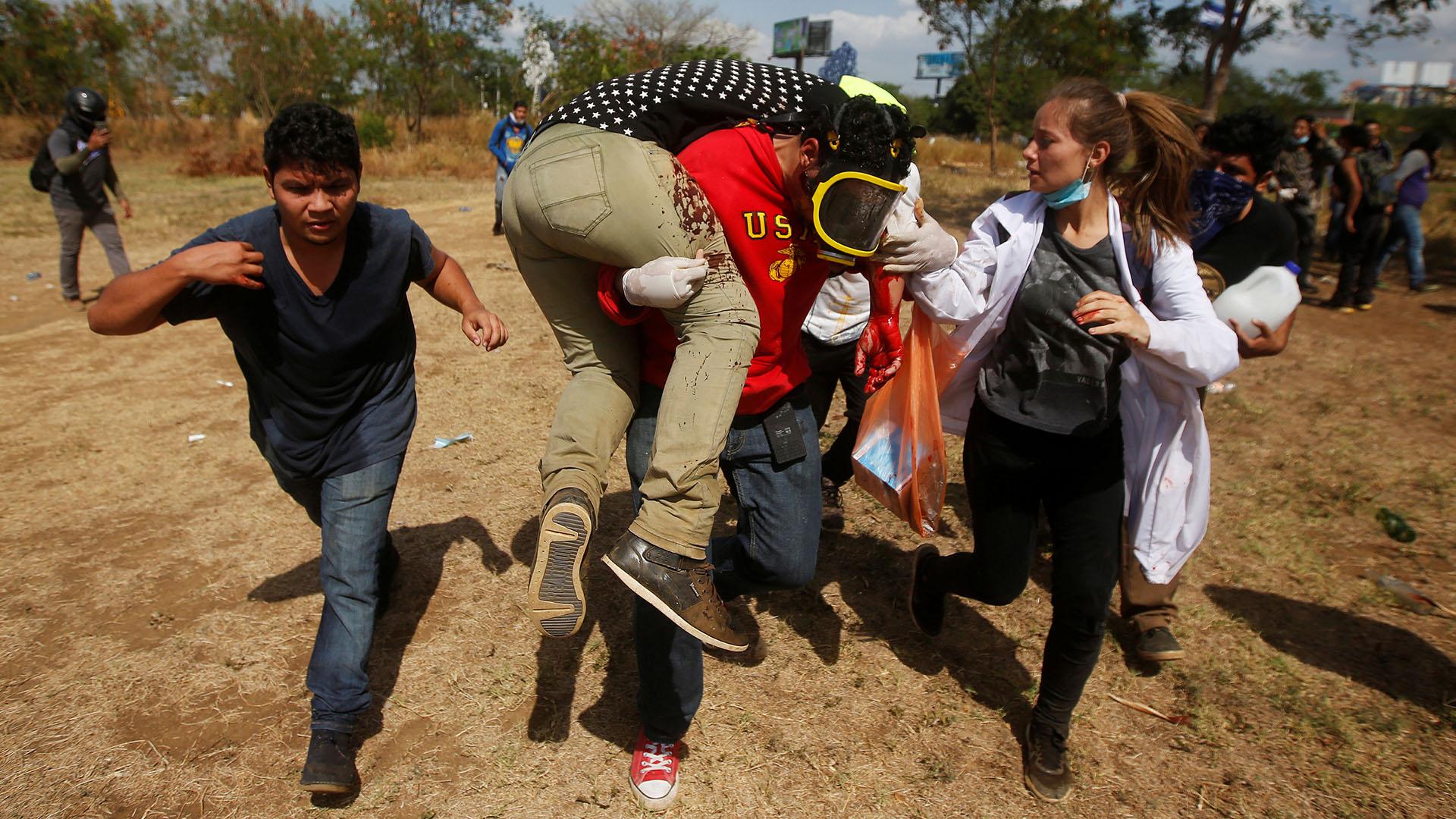 Un manifestante herido es asistido durante una protesta (Reuters)