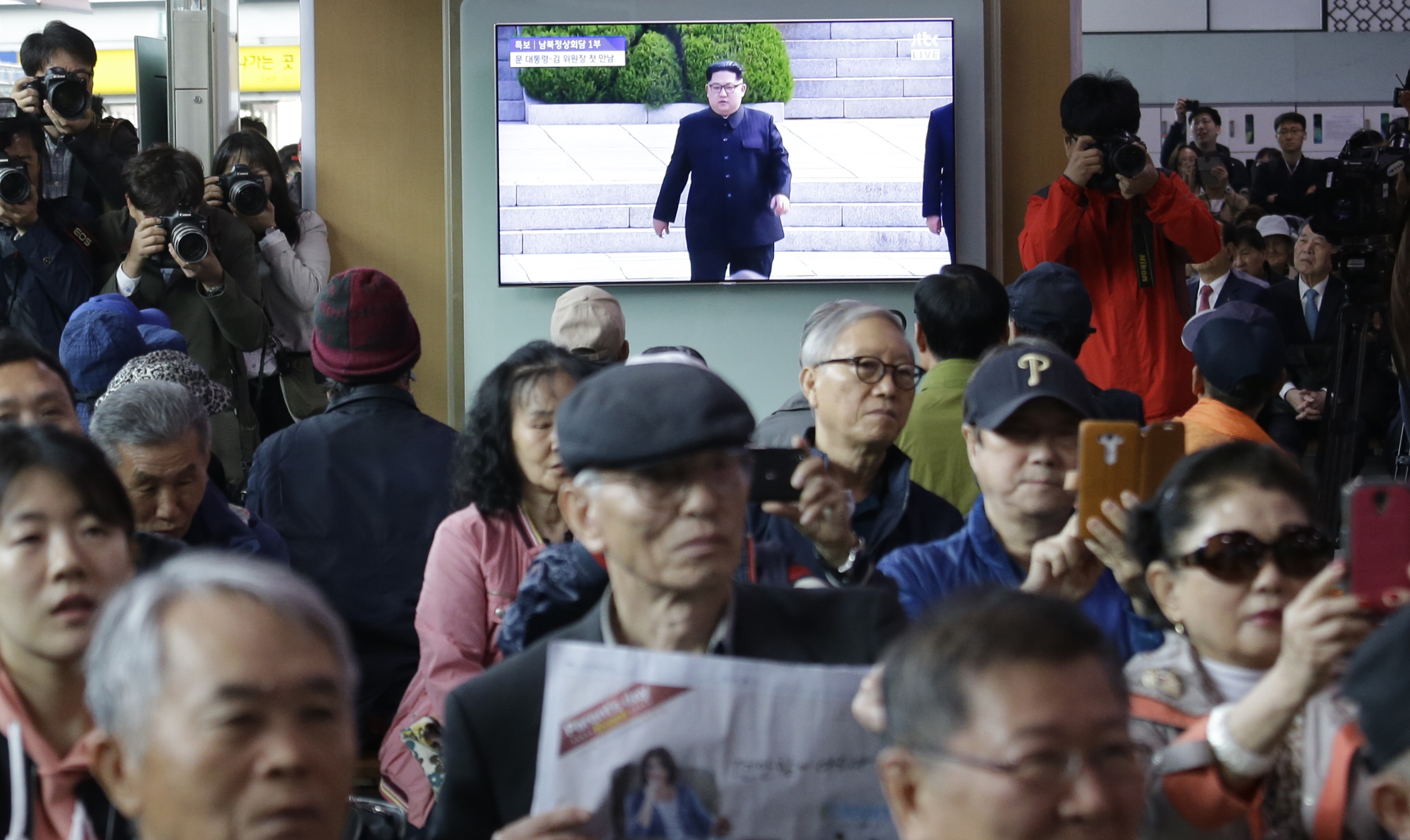 Decenas de personas en la estación de trenes de Seúl observan el encuentro.(AP Photo/Ahn Young-joon)