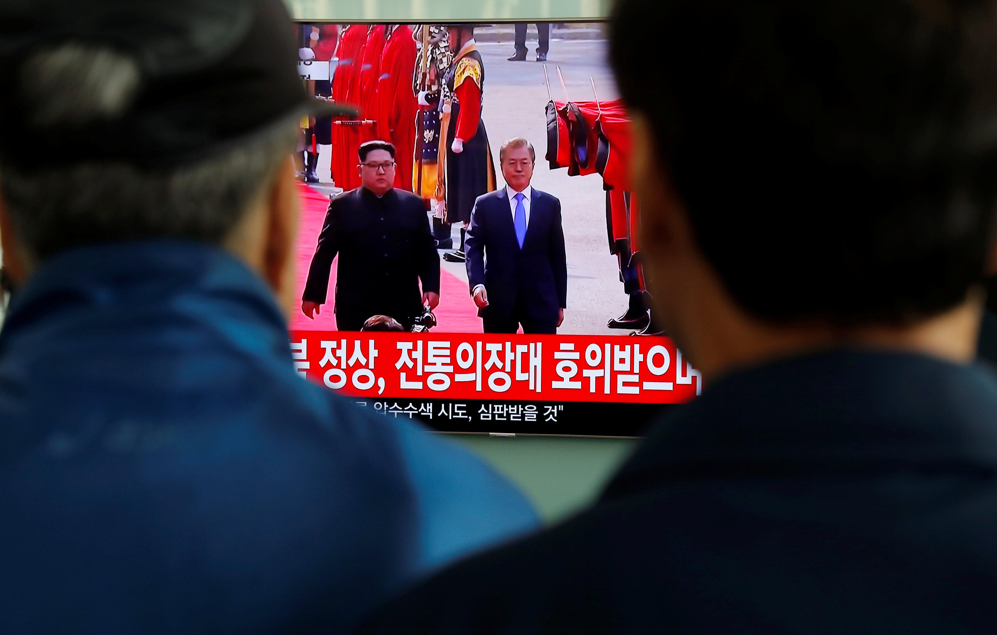 Dos hombre observan el encuentro en la estación de tren de Seúl. (REUTERS/Jorge Silva)