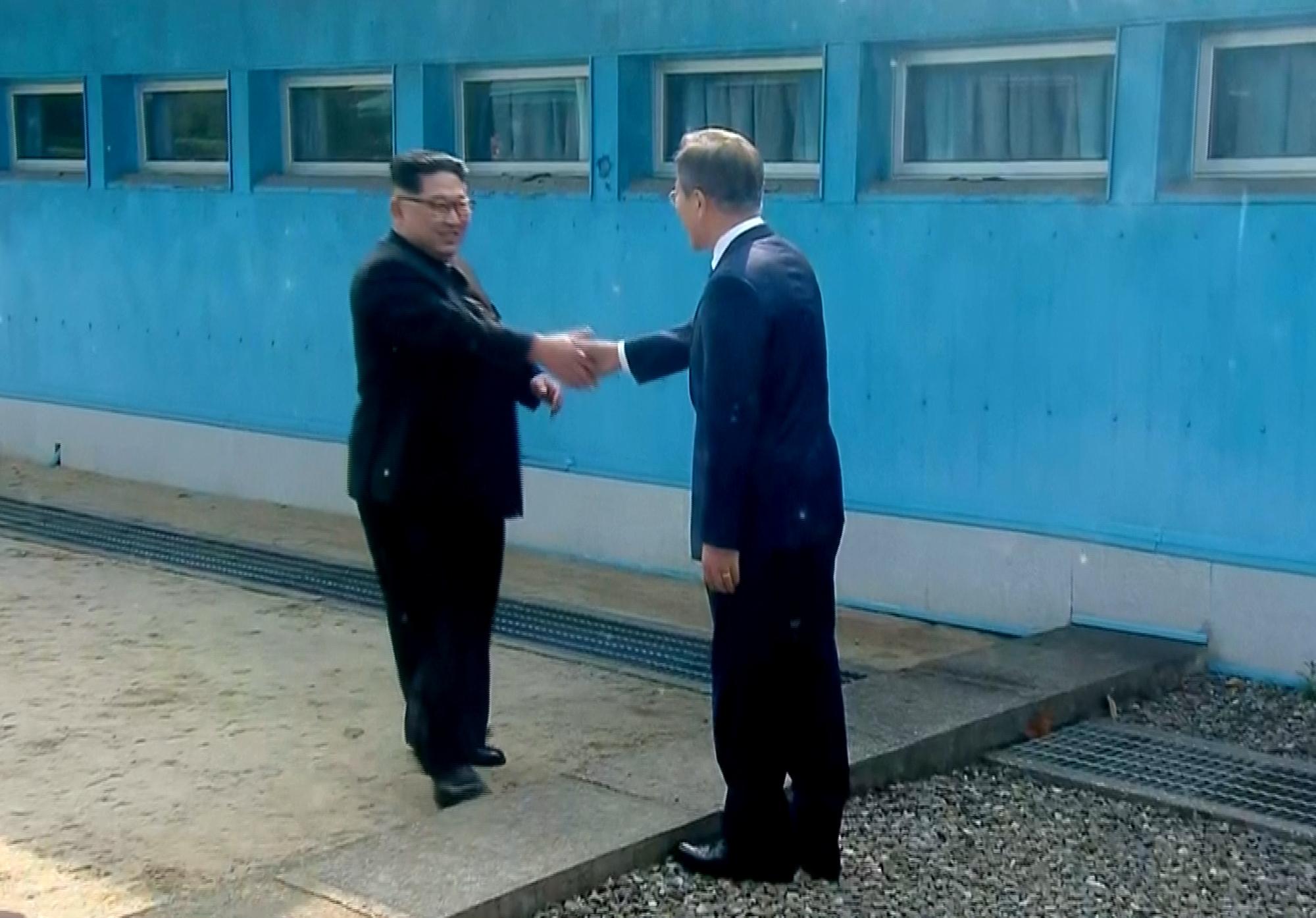 Los dos líderes se dan la mano, cada uno desde lado de su respectivo país.(Korea Broadcasting System via AP)