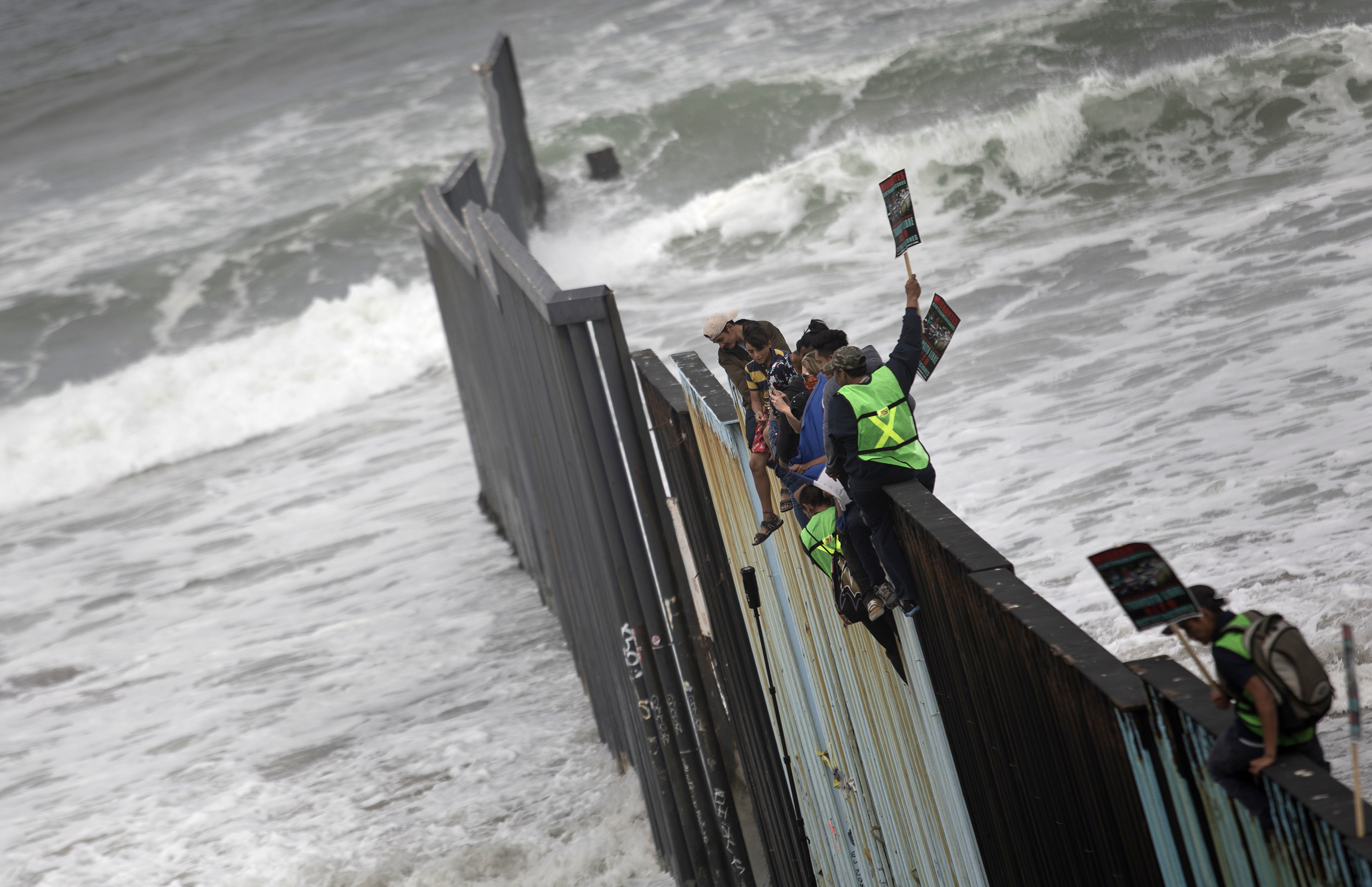 Los migrantes sobre la valla fronteriza en Tijuana(AP Photo/Hans-Maximo Musielik)