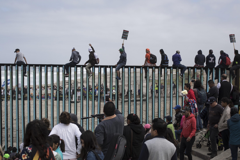 Miembros de la caravana de migrantescentroamericanossobre la valla que separa la frontera entre México y Estados Unidos (AP/Hans-Maximo Musielik)