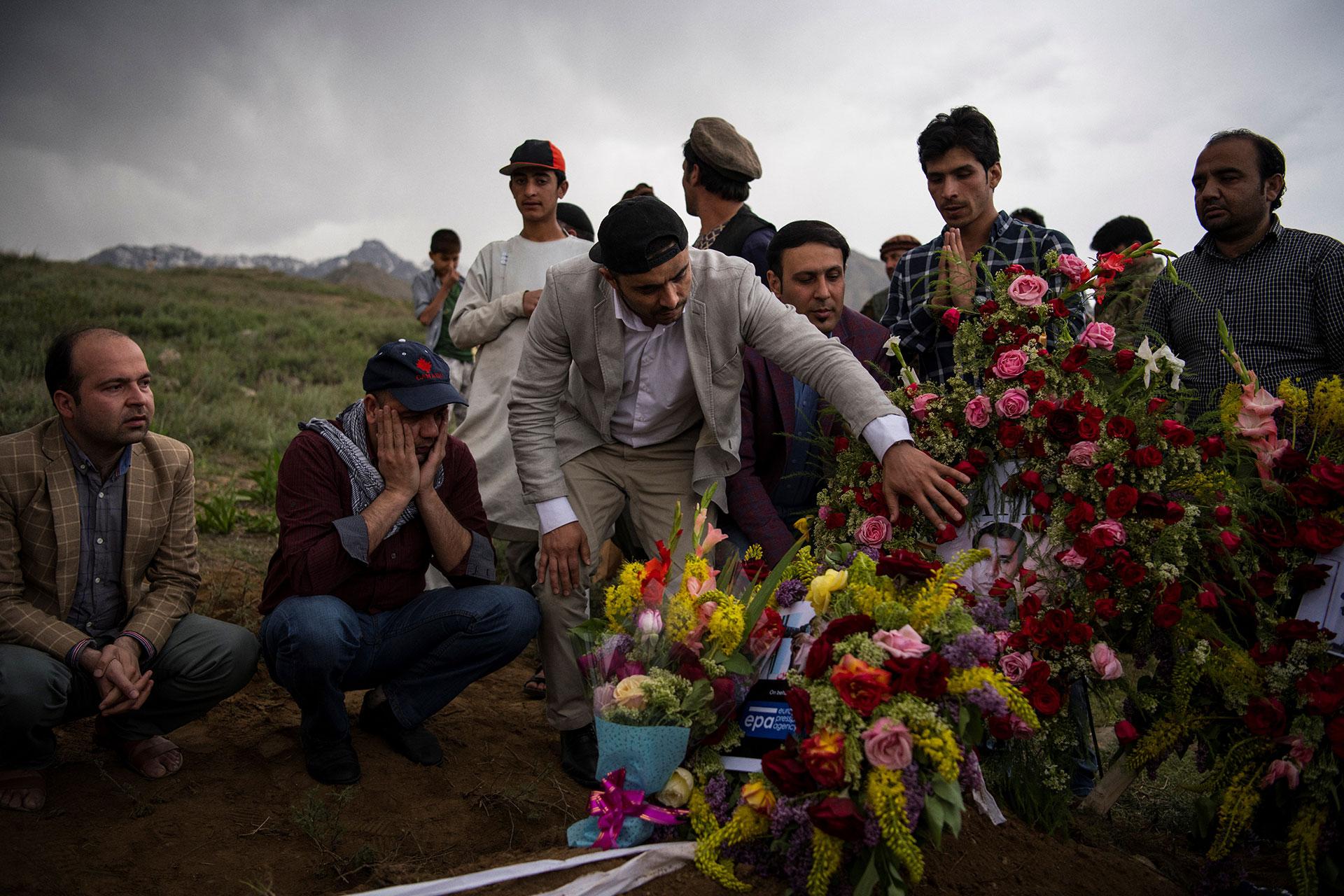 Amigos y familiares del fotógrafo asesinado durante su funeral en Gul Dara, Kabul (AFP)