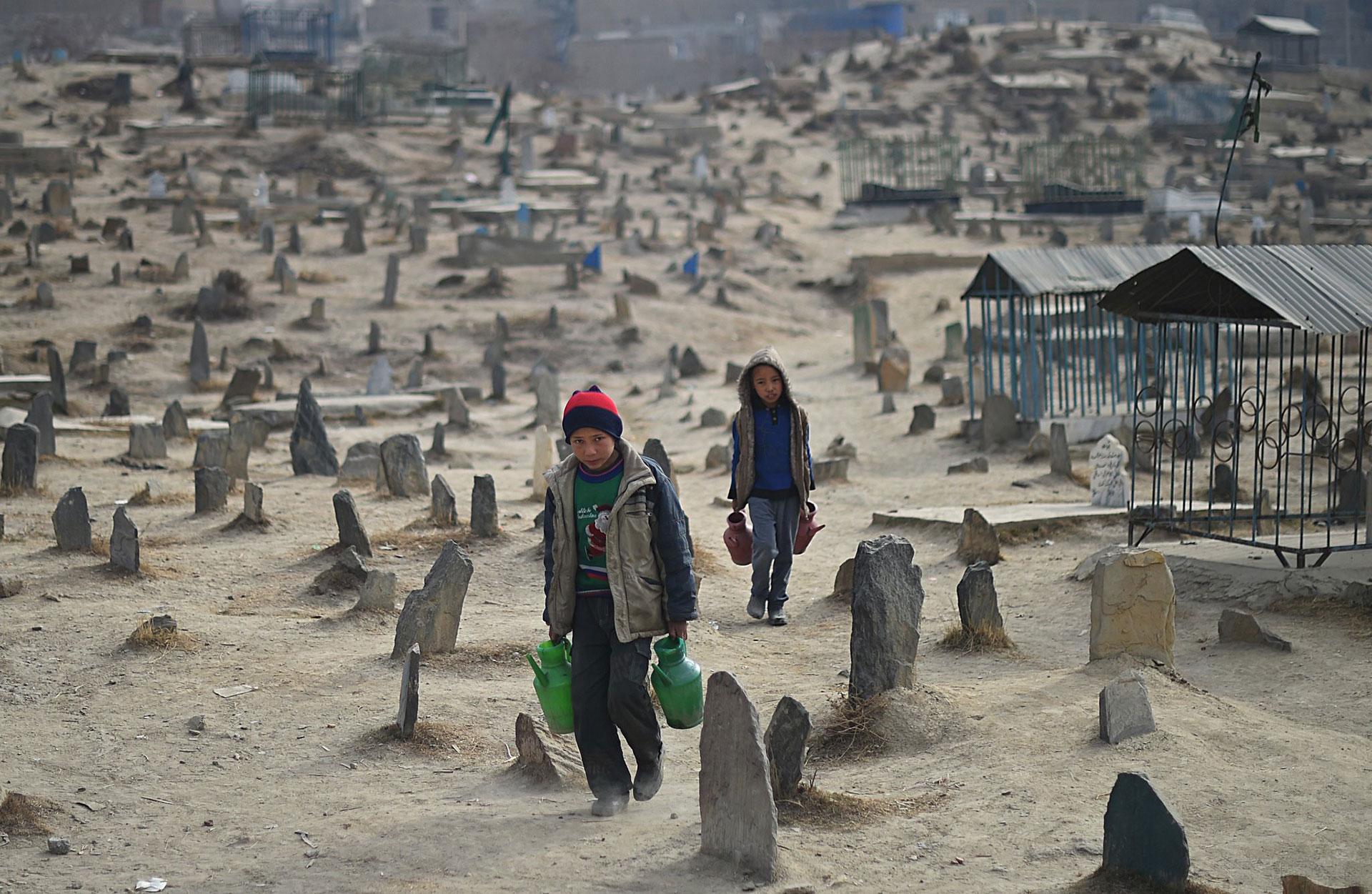 Dos niños que trabajan vendiendo agua recorren un cementerio de Kabul en 2015 (AFP)