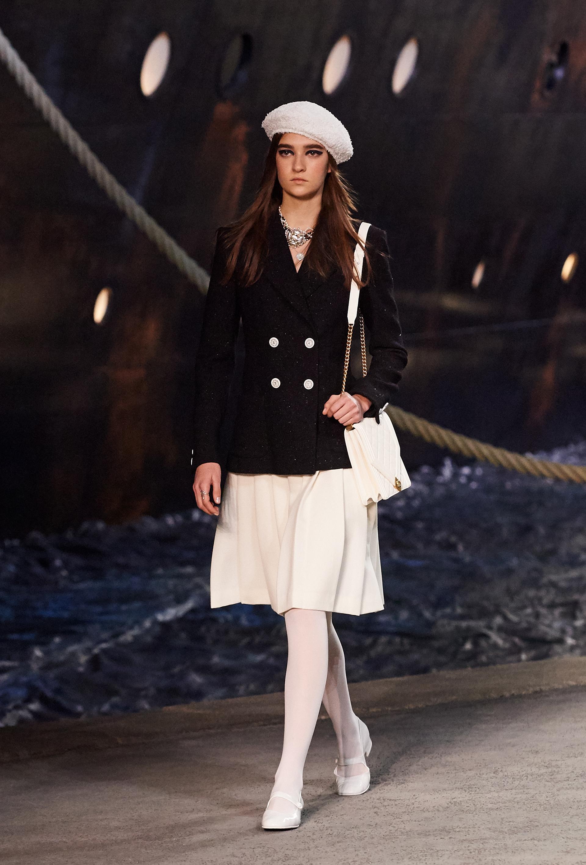 Cartera, boina, medias y zapatos blancos acompañaron el look.