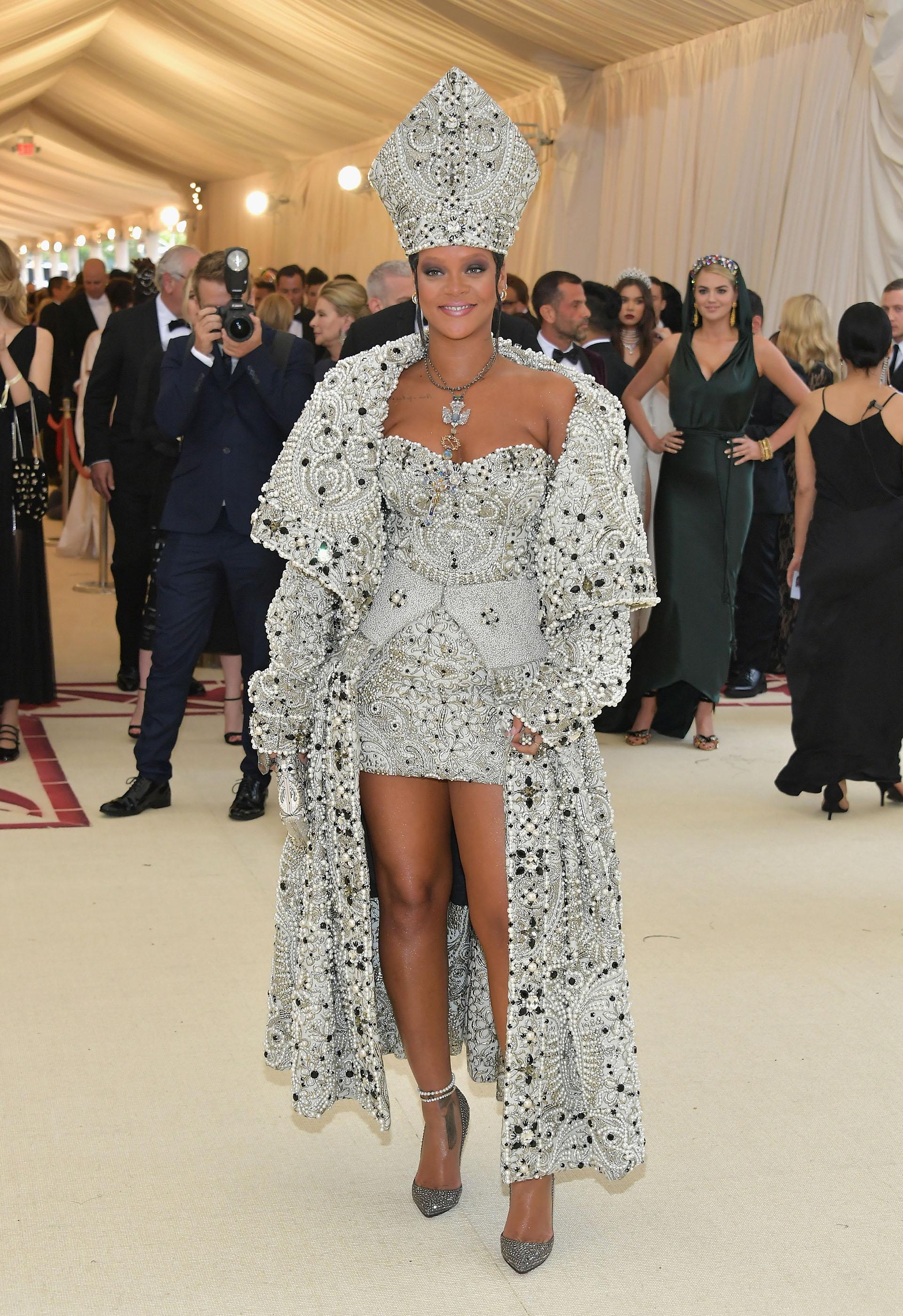 Rihanna siguió la temática religiosa de inspiración papal integramente bordado un diseño deMargiela, un look combinado en mini dress y un opulento abrigo. Una vez más, la cantante obtuvo el premio al mejor vestuario