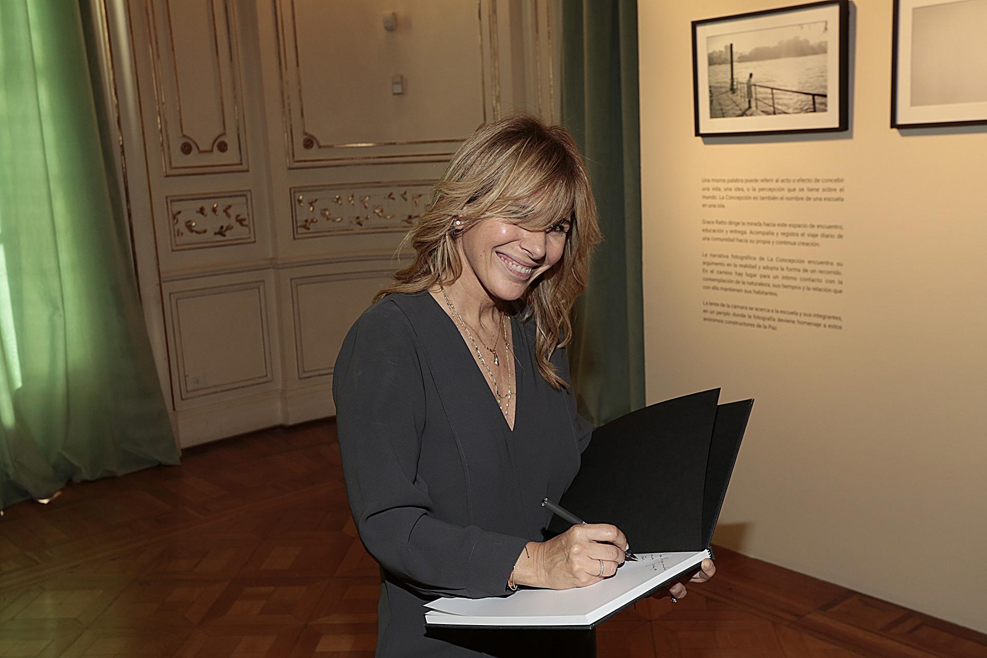 Grace Ratto firmando su libro con más de 40 imágenes en blanco y negro. Lo recaudado por la venta del libro será donado para colaborar con la escuela -La Concepción.