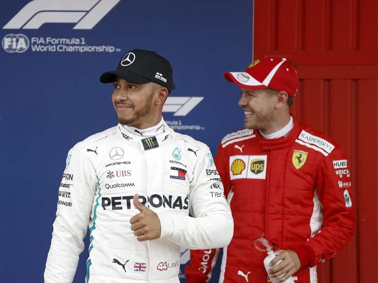 El piloto británico de Mercedes, Lewis Hamilton (i) , que consiguió la pole, junto al piloto alemán de Ferrari, Sebastian Vettel, que fue tercero (d), celebran los puestos obtenidos en los entrenamientos oficiales de la Fórmula Uno en el Circuit de Barcelona-Catalunya (EFE)
