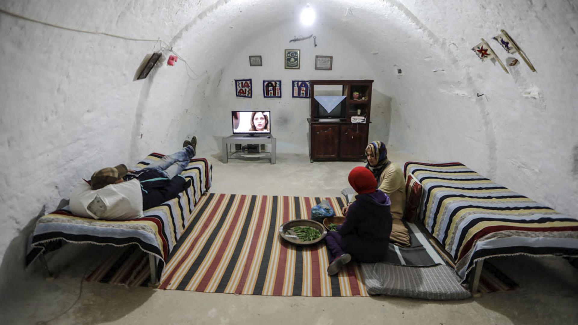 Madre e hija pelan vainas de guisantes mientras el hijo mira televisión