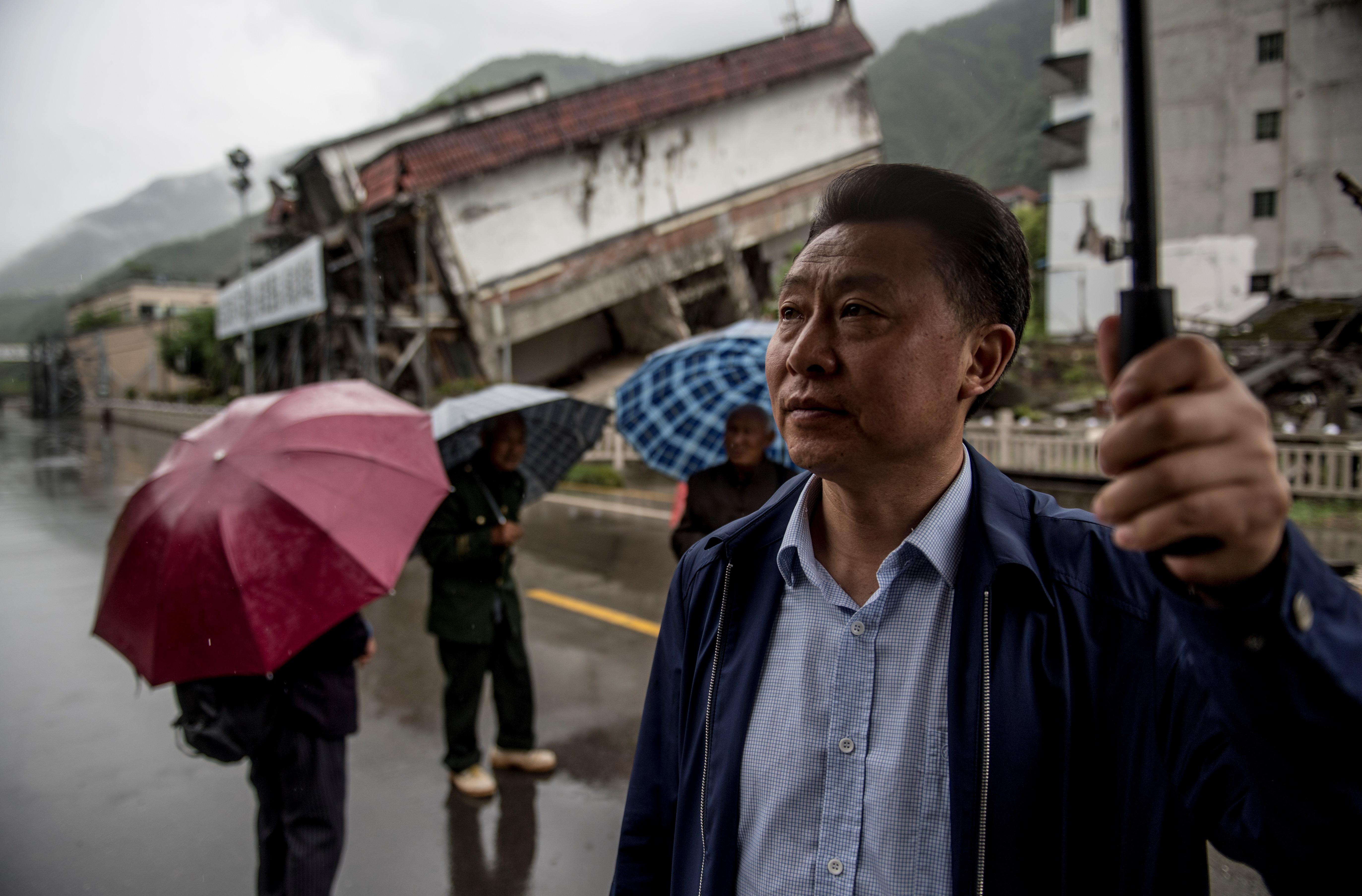 Chen Guoxing frente a las casas destruidas por el sismo (AFP / Johannes EISELE)