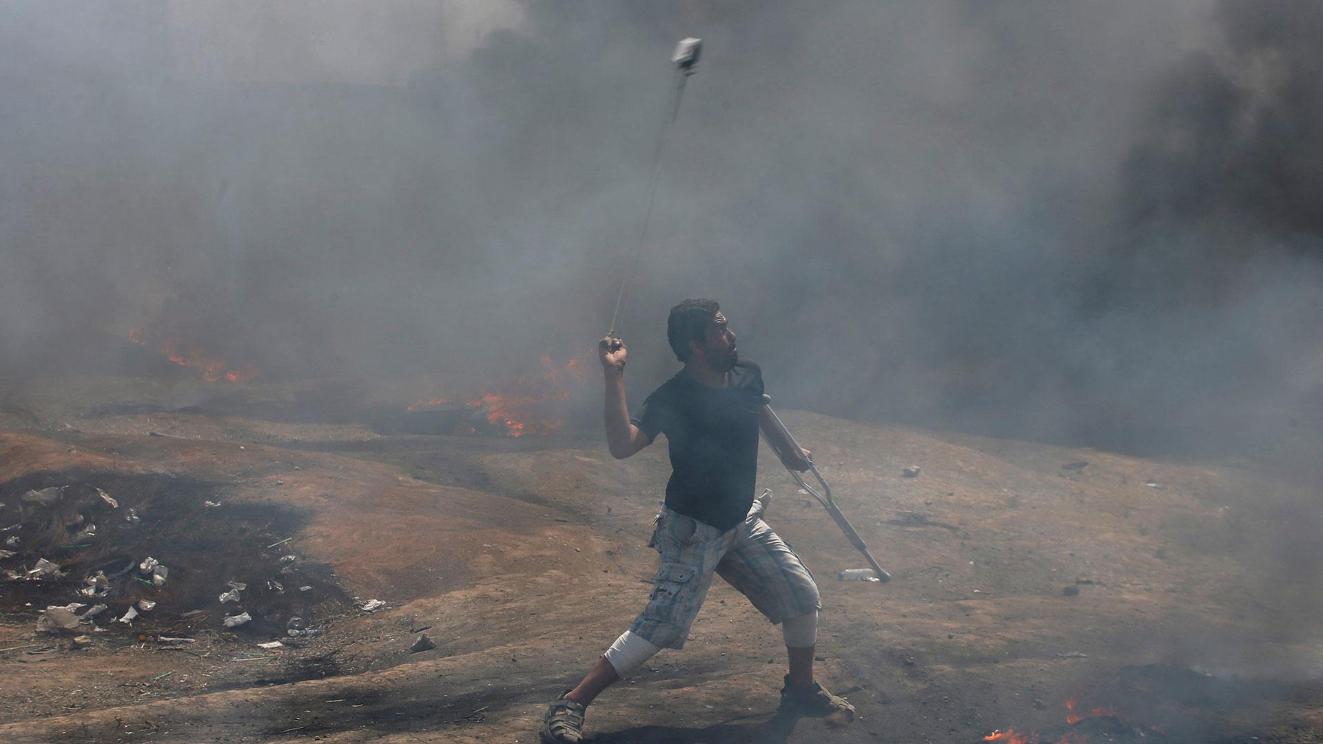Un hombre lanzando piedras contra los soldados israelíes en Gaza (Reuters)