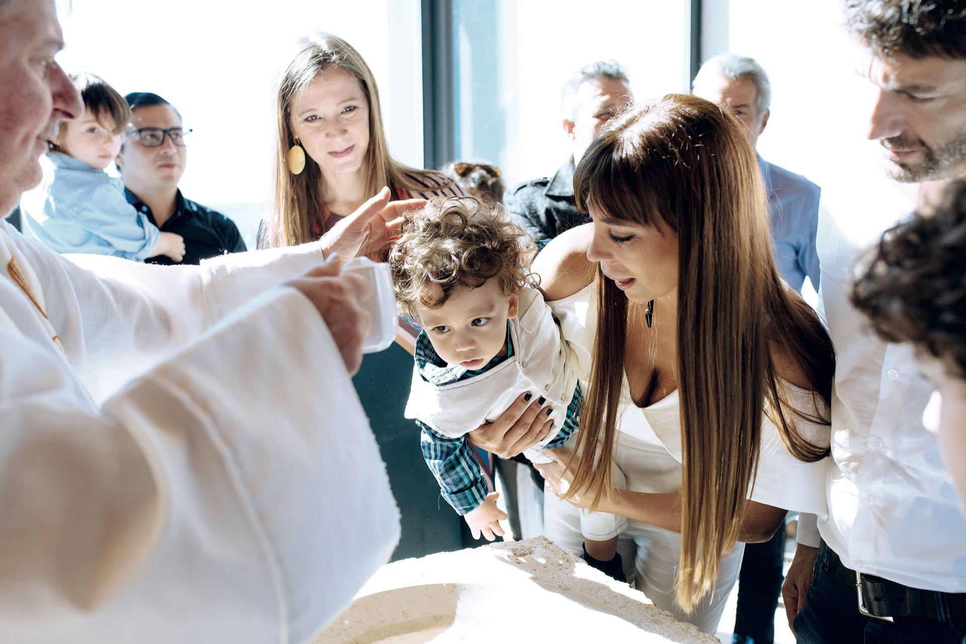 El padre Damián unge al niño, en brazos de su madre Ximena, bajo la mirada de su papá y su madrina