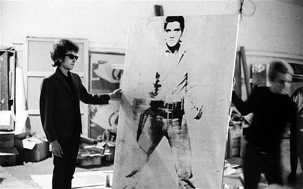 """Bob Dylan ayuda a Warhol a sostener el retrato """"Double Elvis Ferus Type"""". La foto es de 1965"""