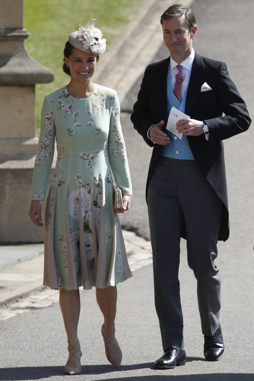 Pippa y su marido James Matthews a la entrada de la Capilla. Ella lució un vestido en verde agua, sandalias Jimmy Choo, y un discreto tocado de flores (AP)