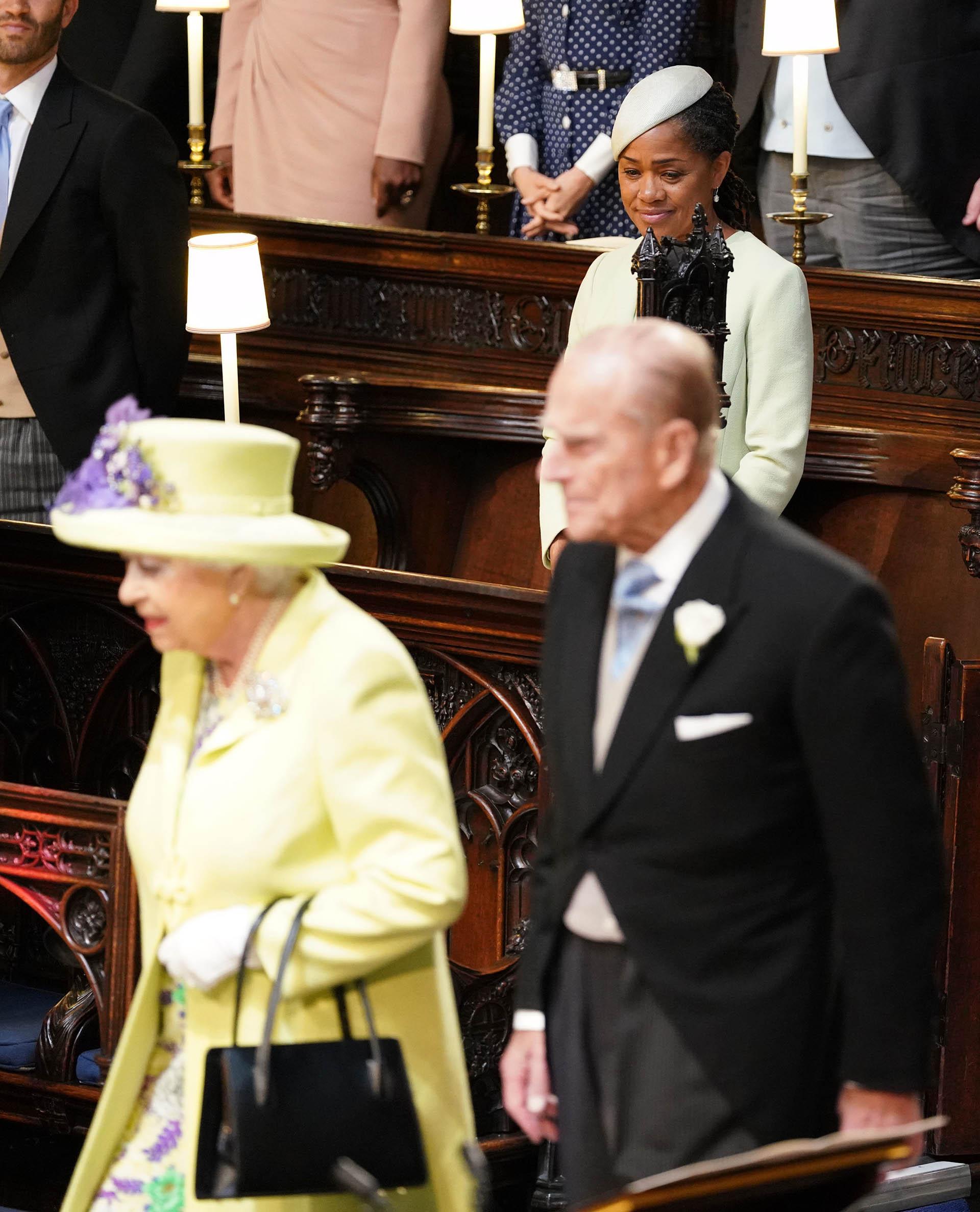 La entrada de la Reina Isabel II y Felipe de Edimburgo a la capilla de St. George. Detrás, emocionada, la madre de Meghan Markle (AFP)