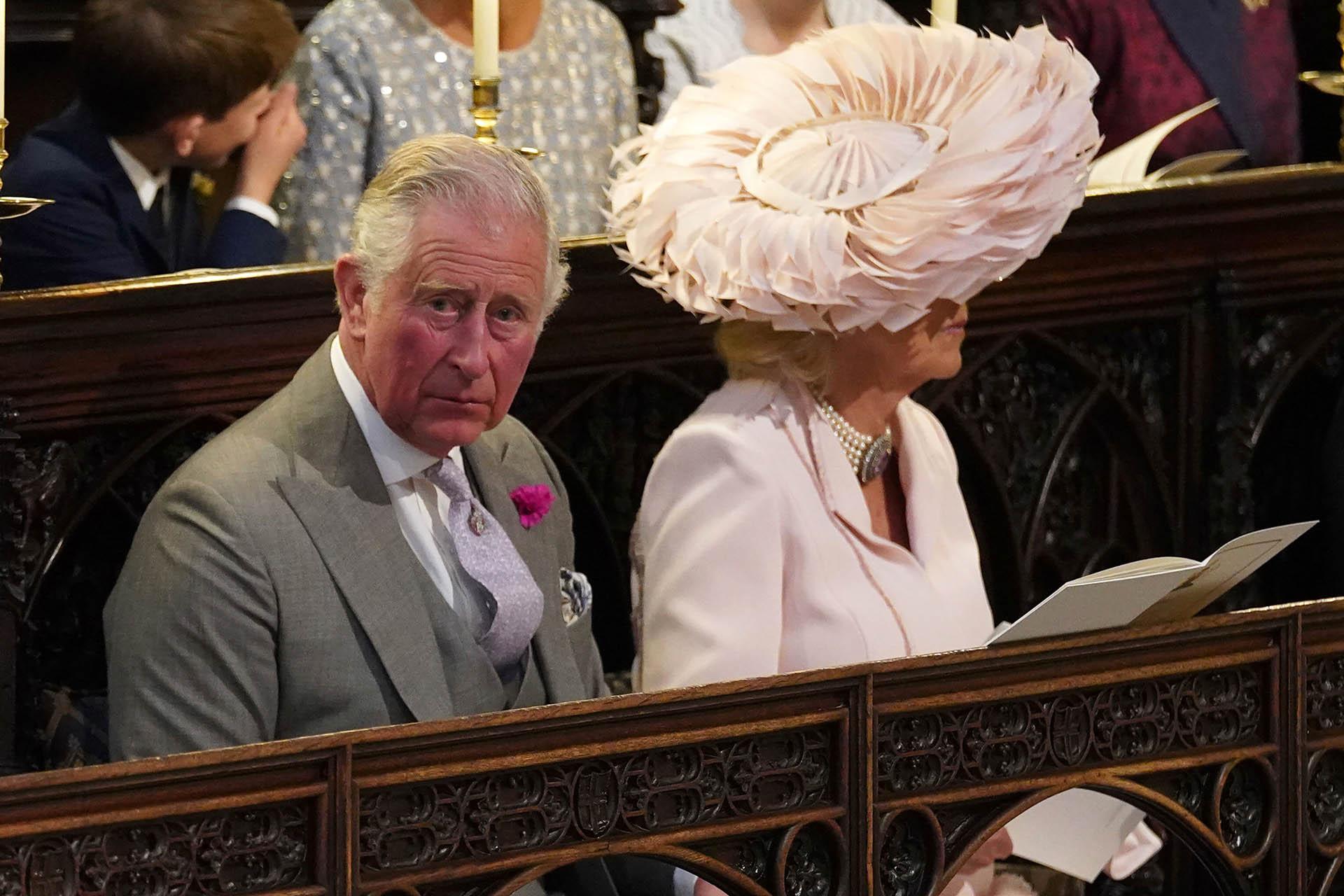 Carlos y Camila.Ella llevó un amplio sombrero de plumas en rosa palo(AFP)