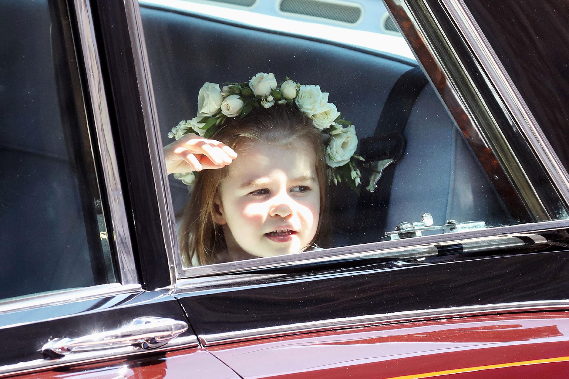 La sobrina del príncipe Harry y dama de honor, Charlotte -hija de William y Kate Middleton- saluda a la gente que espera fuera de la capilla (AFP / Chris Jackson)
