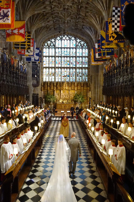 A la mitad de la nave de la Iglesia la esperó el príncipe Carlos, quien la llevó al altar. El padre de la actriz, Thomas Markle, no estuvo en la boda por razones de salud. Pero muchos afirman que la familia real había visto como inadmisible que se hubiera prestado a escenificar fotos para unos paparazzi y luego venderlas (AFP)