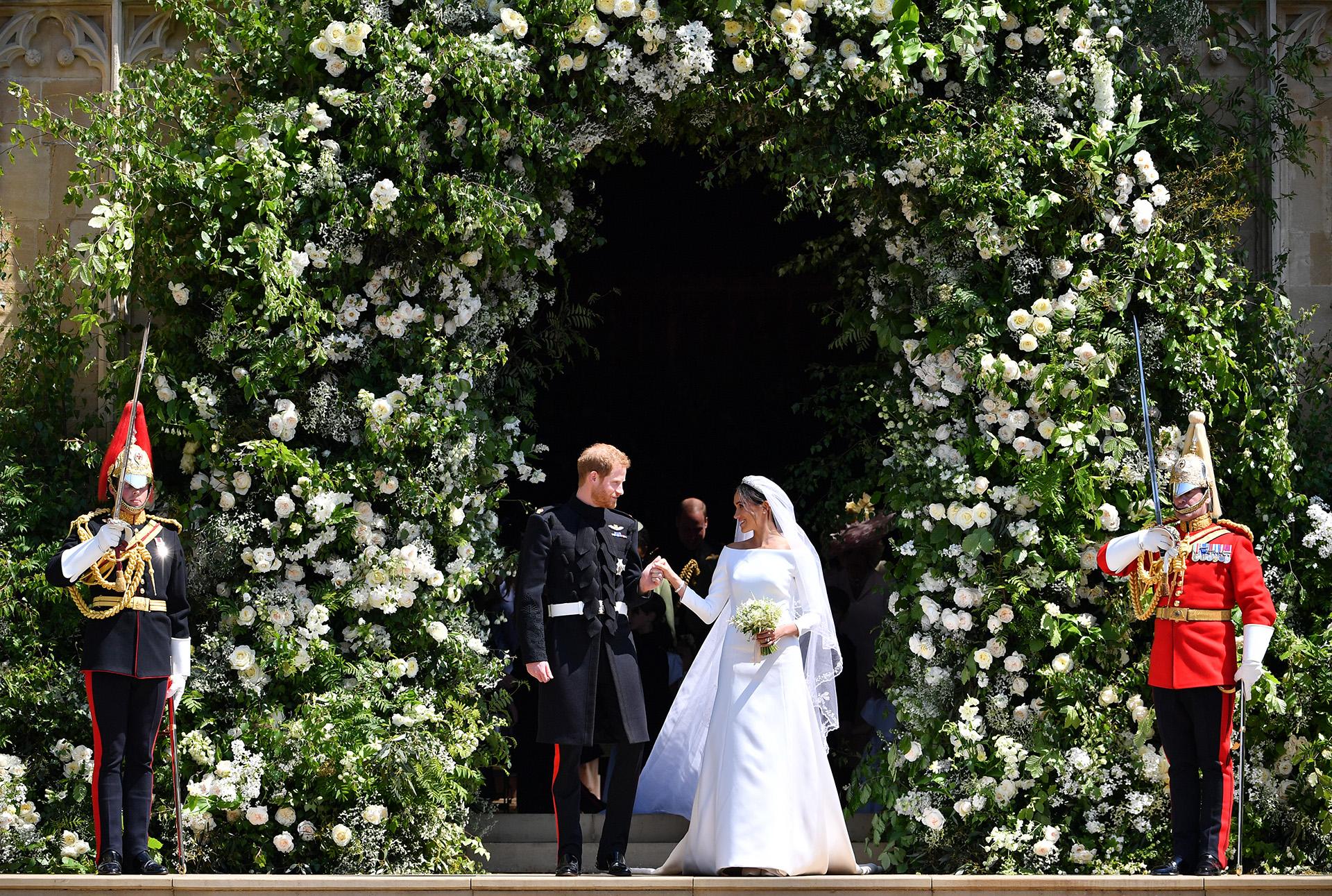 Recién casados, ante 1.200 invitados. Los duques de Sussex debajo del arco formado por cientos de flores blancas que decoraban la capilla del Castillo de Windsor (AFP)
