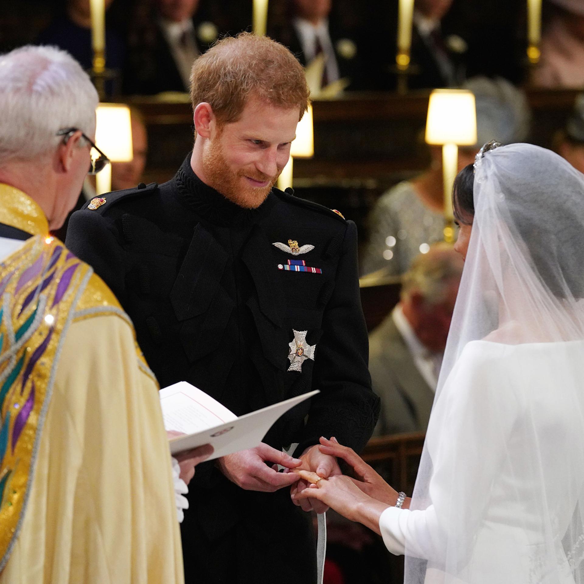 Otra toma del momento en que el príncipe Harry le pone la alianza a Meghan.