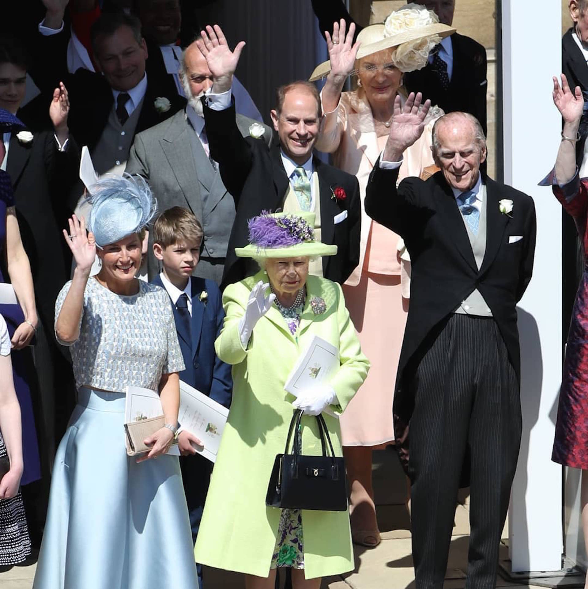 La reina Isabel II y su esposo Felipe, que fue recientemente operado de la cadera y se especuló con su presencia en la boda, saludan a los novios que se alejan en el carruaje.
