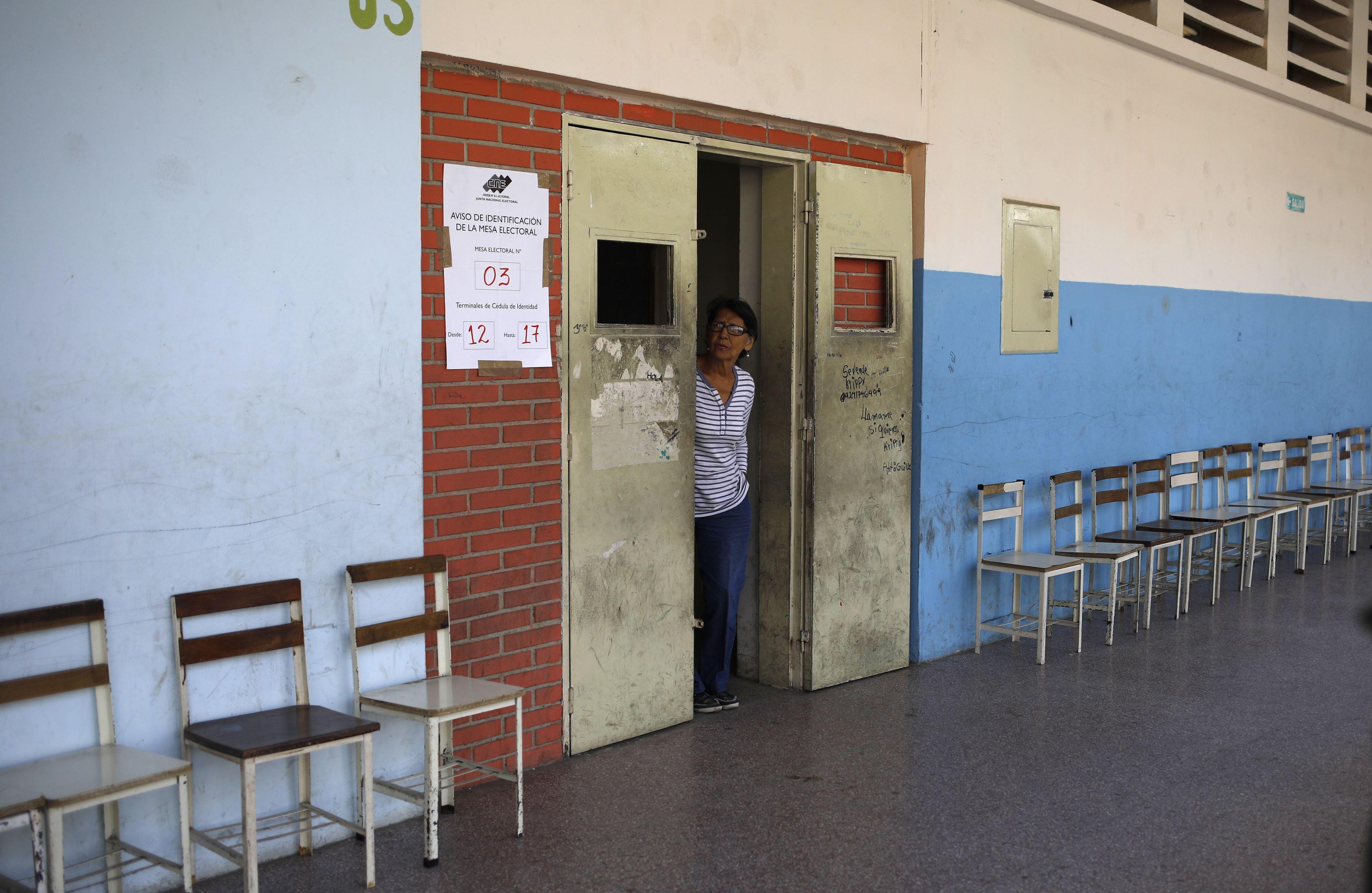 Una mujer se asoma para ver si algún votante se acerca a la mesa