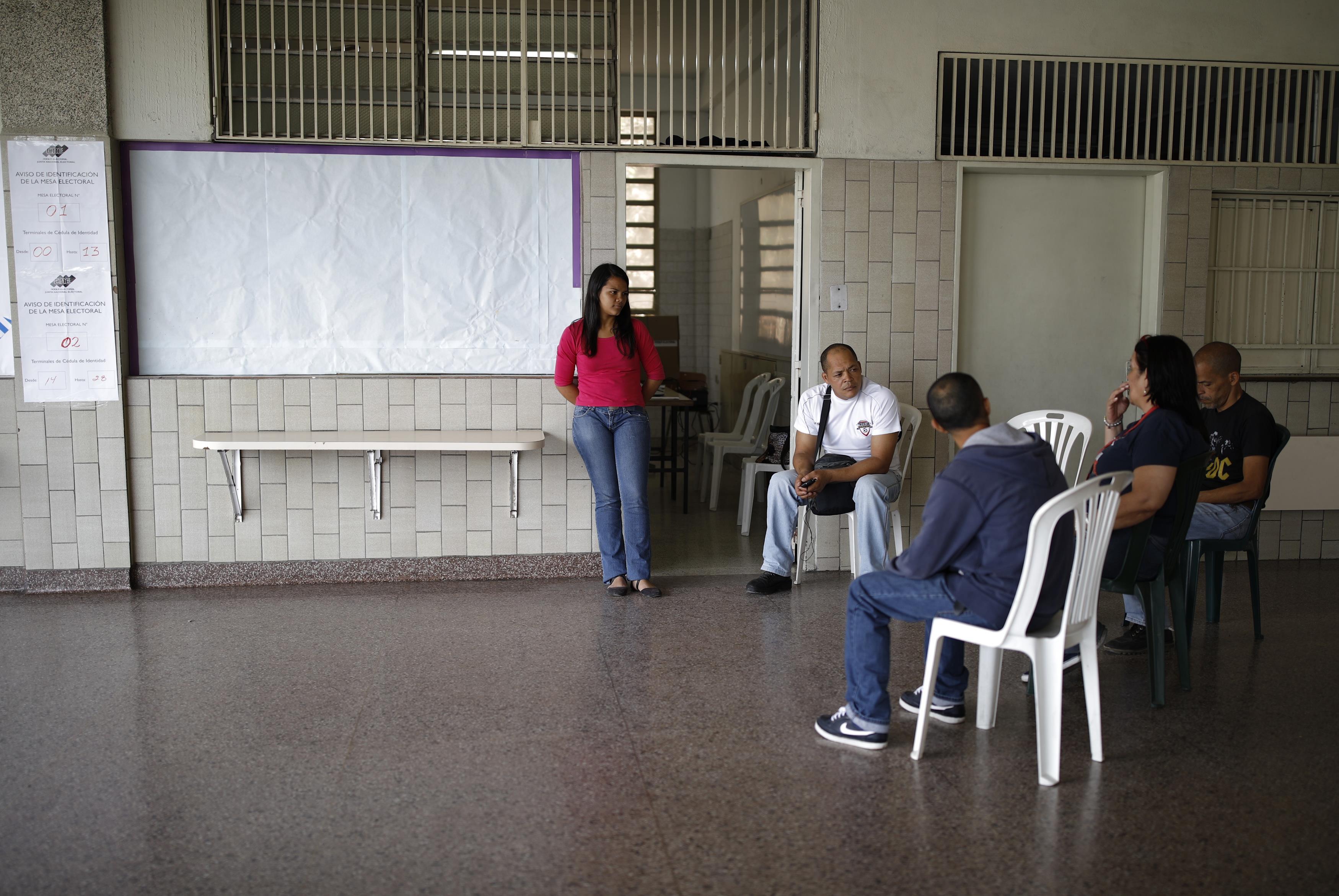 Miembros de una mesa conversan y se distraen mientras esperan a votantes (Reuters)