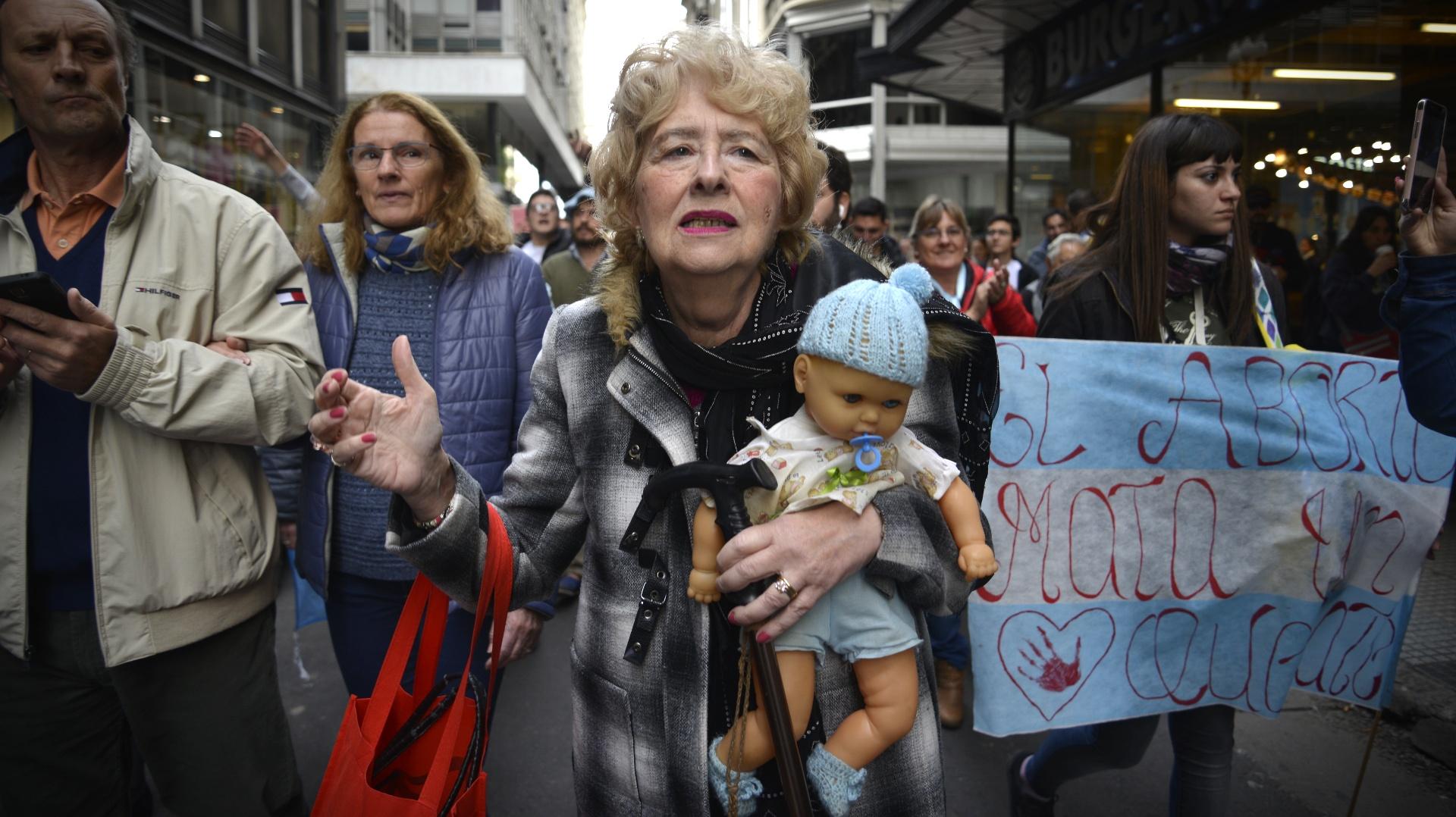 Una de las participantes de la marcha sosteniendo un bebé de juguete