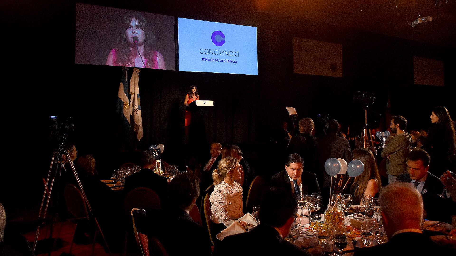 Gastón Corral, director de Sustentabilidad Corporativa de HSBC Argentina, y Sergio Massa escuchan el discurso de Beby Lacroze durante la cena anual de Conciencia