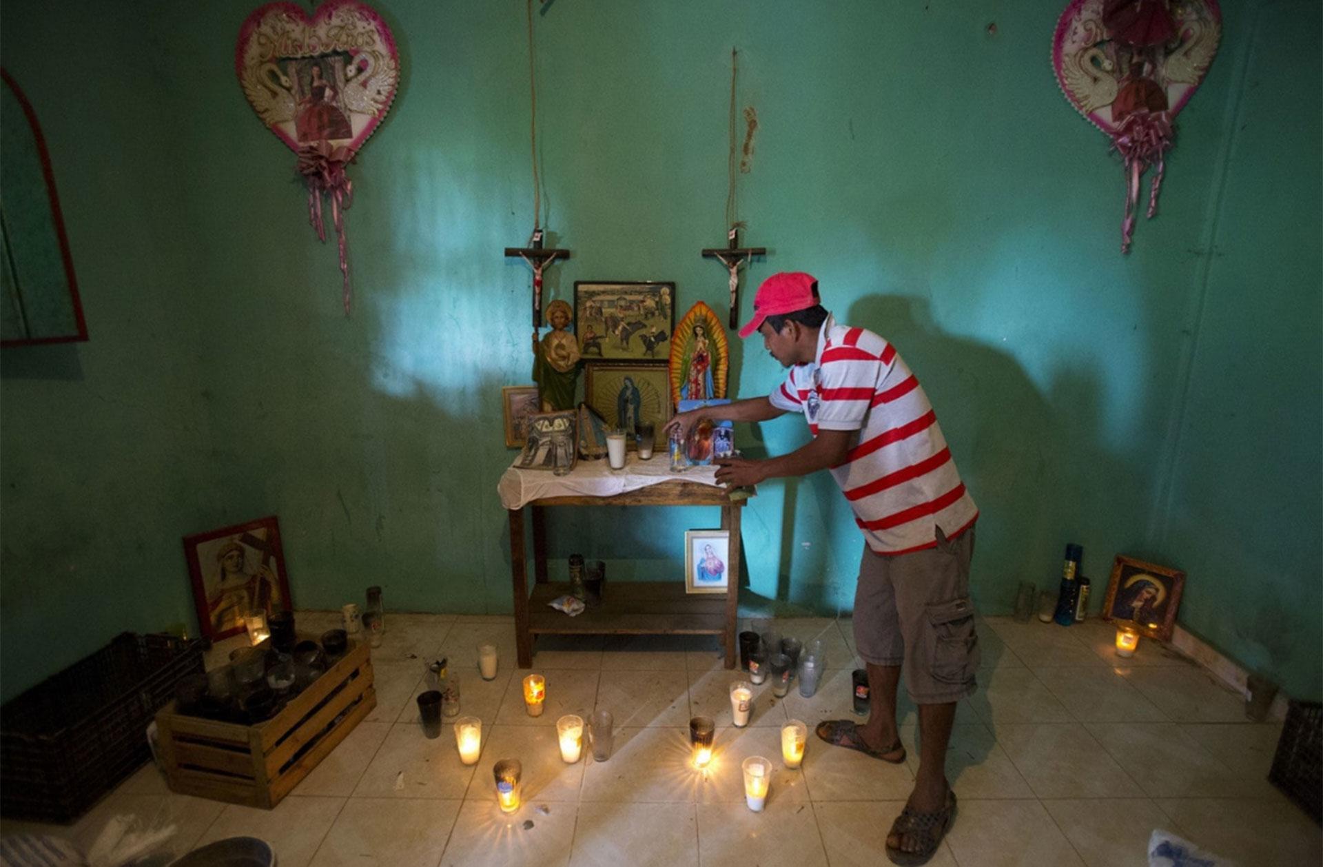 Un familiar ordena un altar en honor a Alexis Estrada Asencio, quien murió en un tiroteo afuera de una comisaría en La Concepción