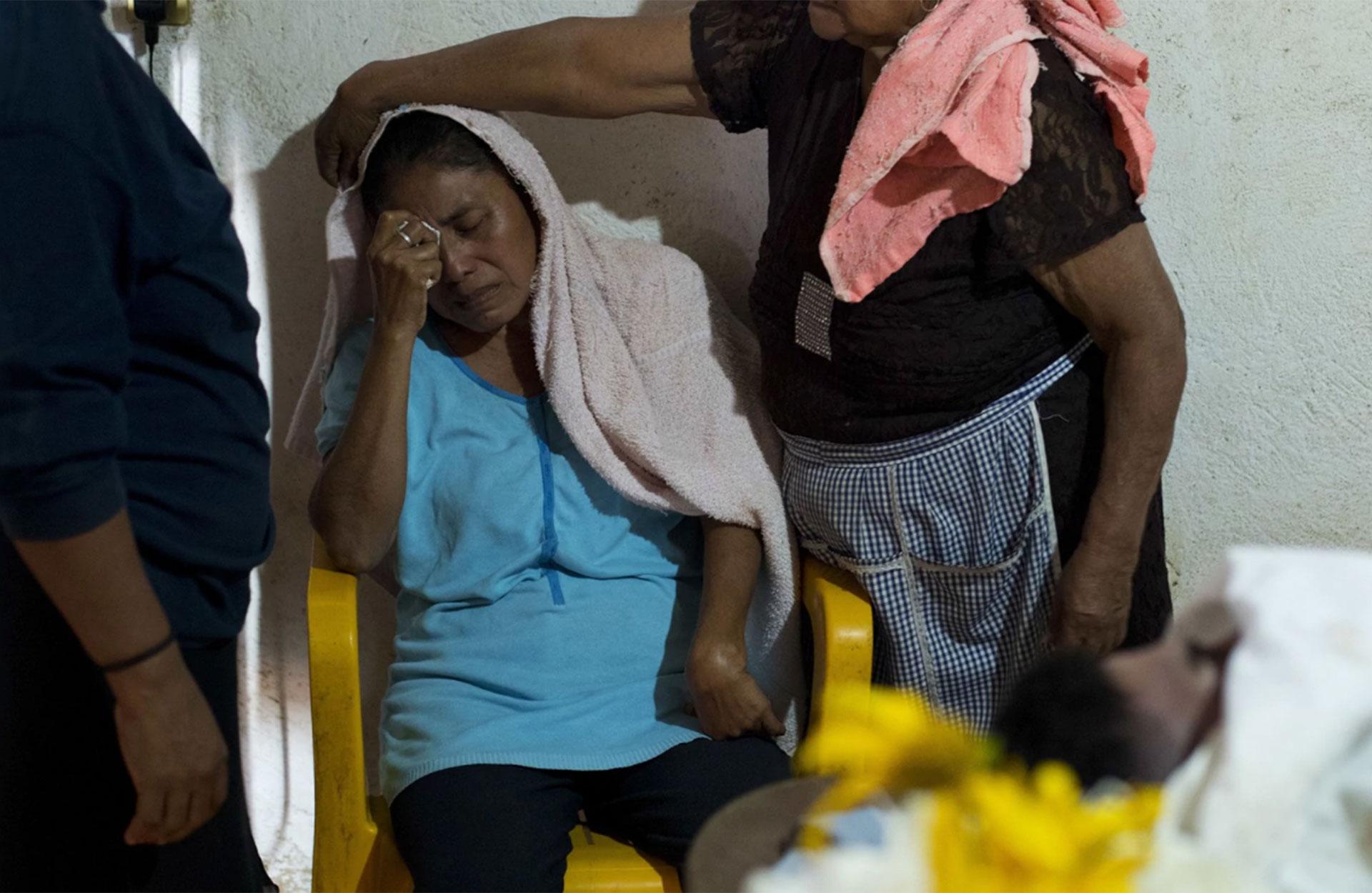 Un familiar consuela a la madre de Daniel Julio, un policía comunitario fallecido en Huamuchapa