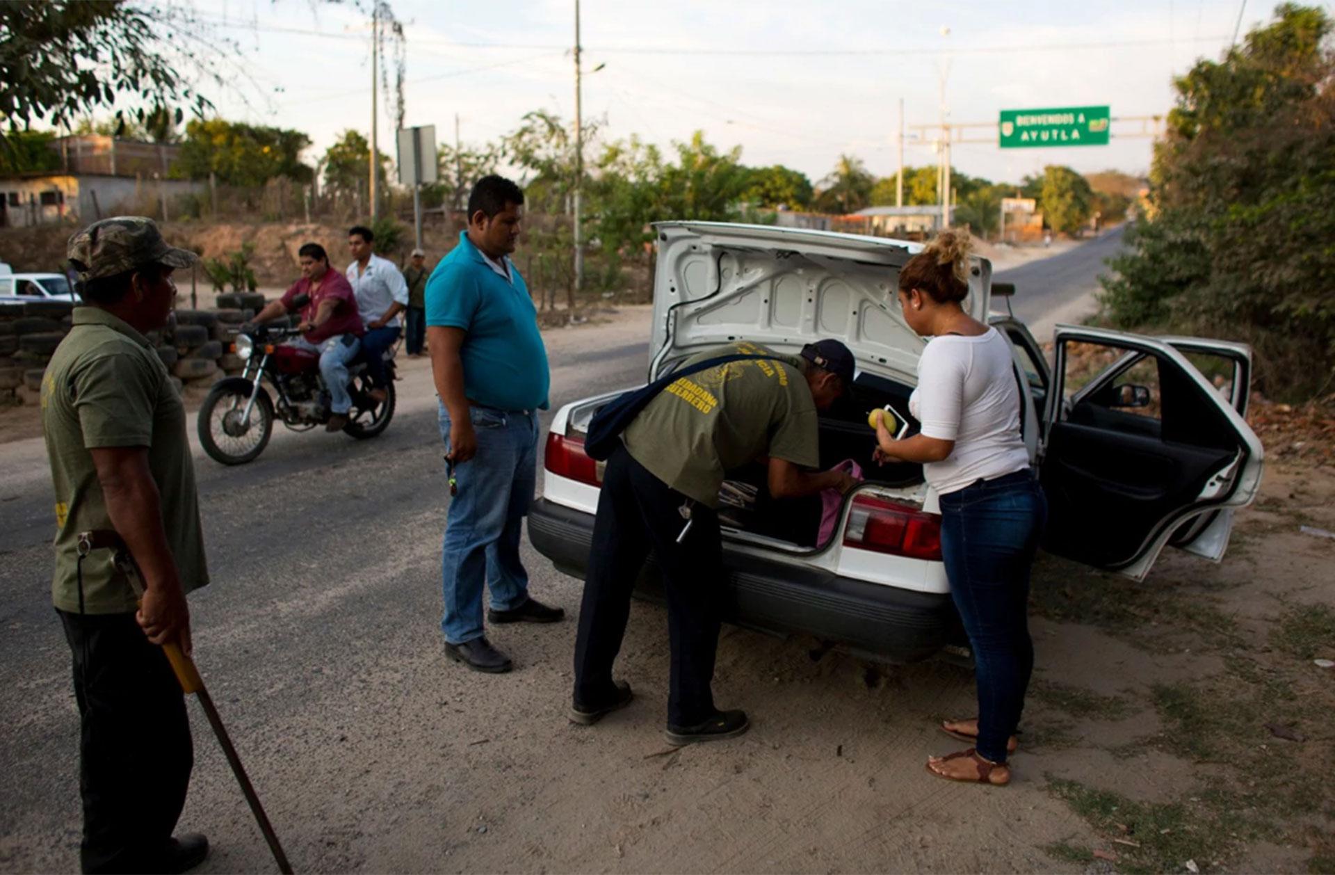 Miembros del grupo revisan la carga de un taxi en un control rutinario por las rutas a las afueras de Ayutla de los Libres