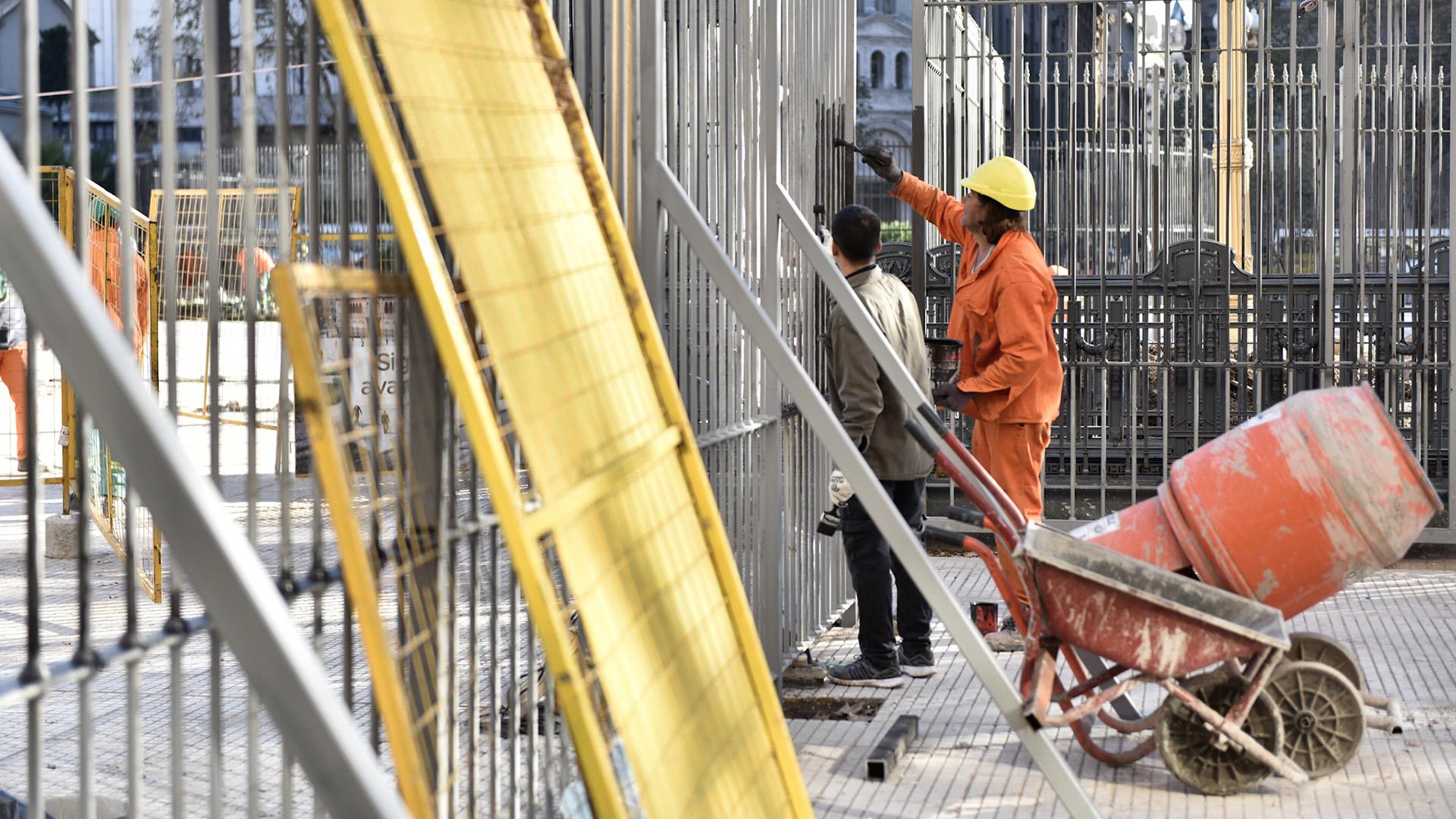 Dos obreros pintan las nuevas rejas