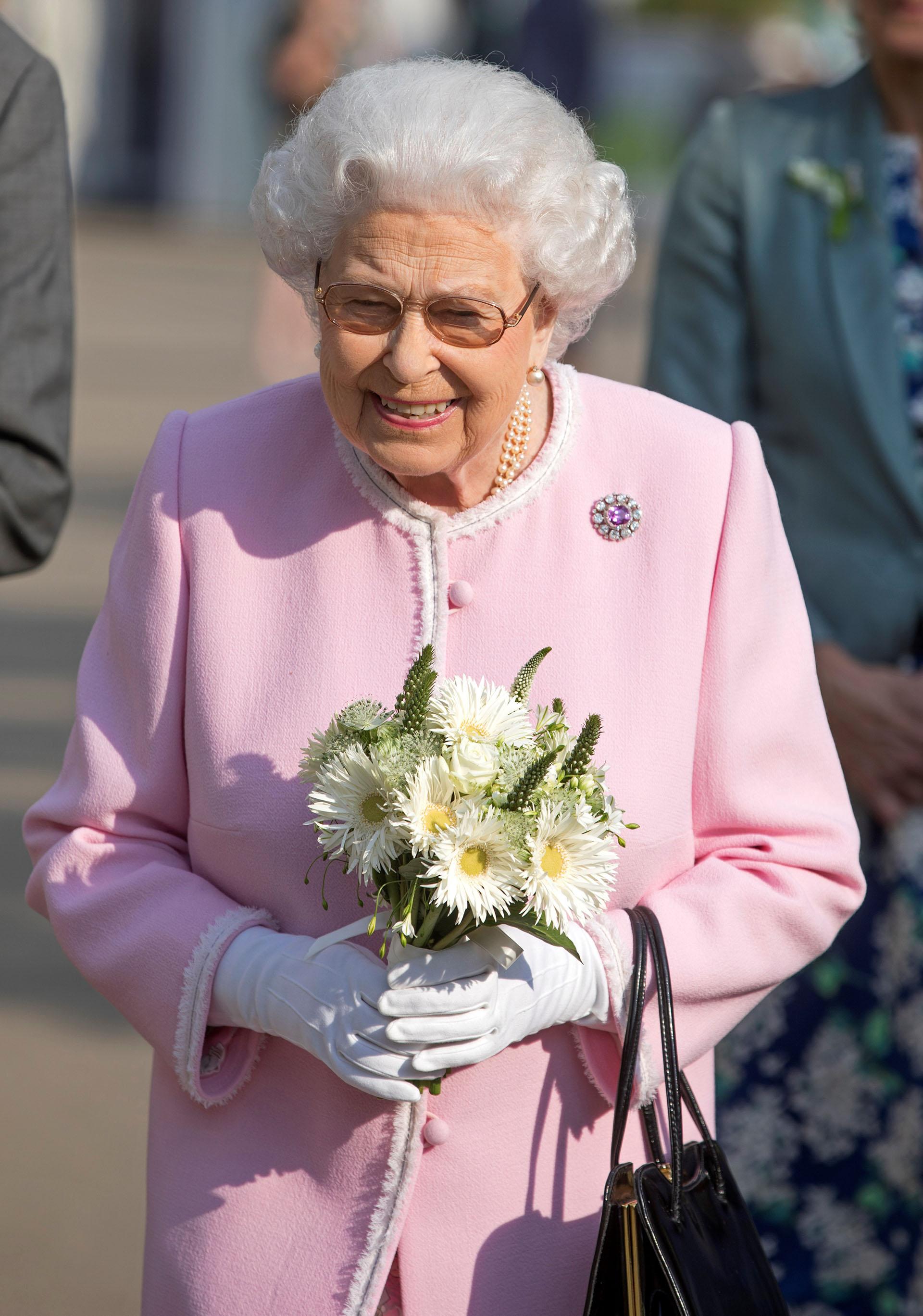 La reina paseó por los jardines con un ramo de flores en sus manos