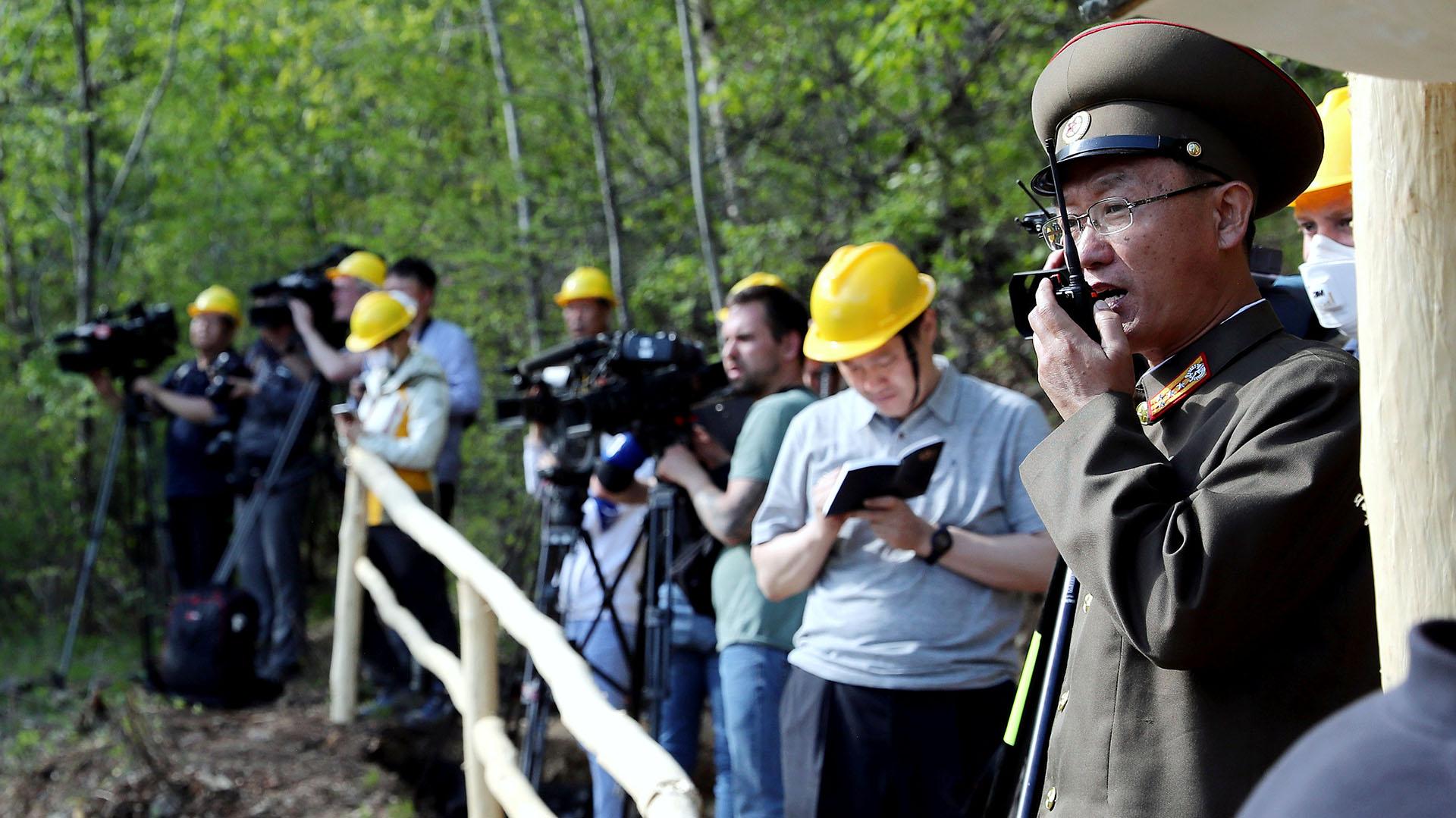 Un oficial del Instituto de Armas Nucleares de Corea del Norte se comunica con un operador para detonar uno de los túneles. La dictadura de Kim Jong-un no ofreció datos sobre los militares que formaron parte de los operativos (Reuters)