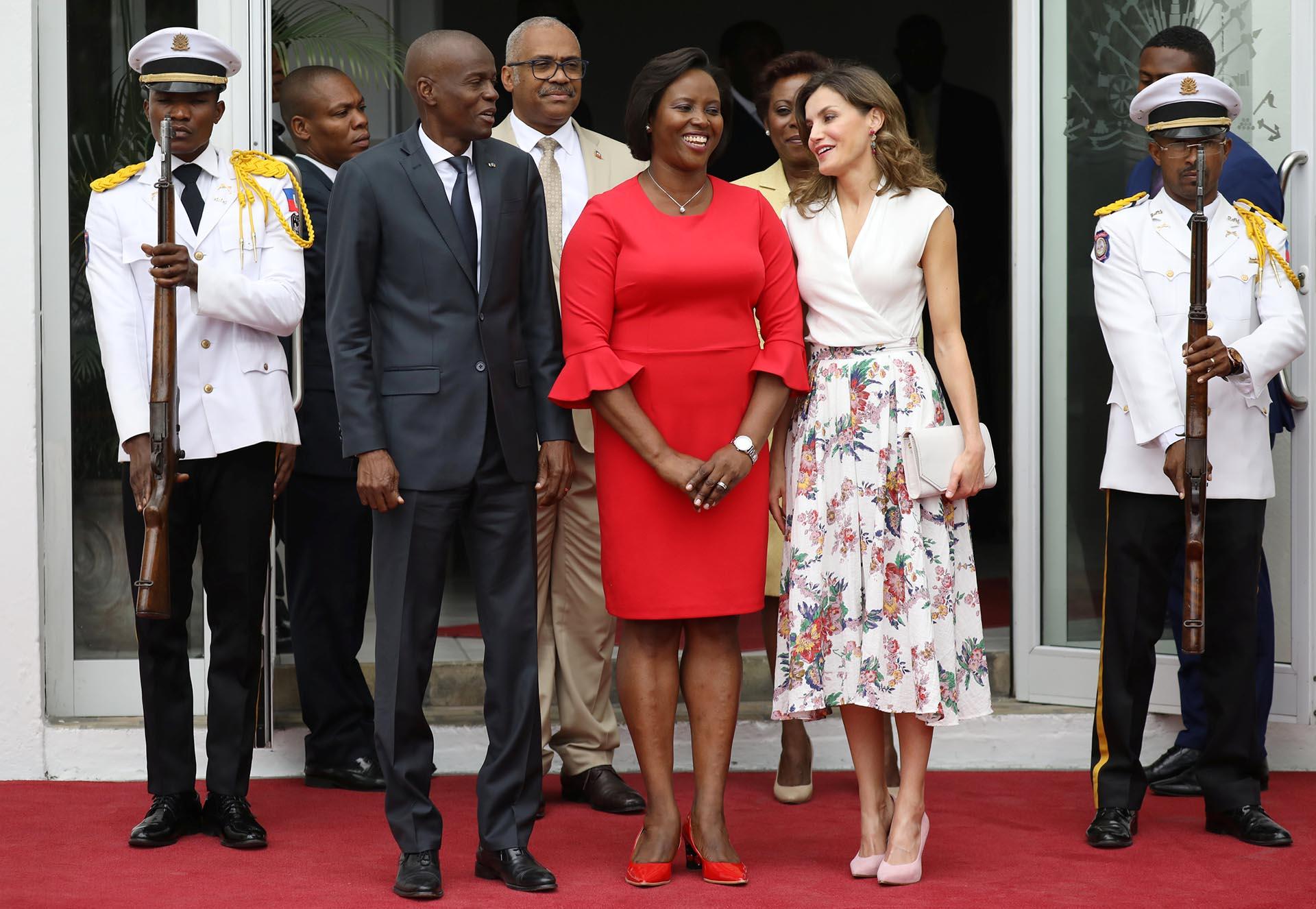 Letizia, acompañada por el presidente de Haití, Jovenel Moise, y su mujer. La monarca eligió un look sencillo pero elegante, acorde a un compromiso diurno. Su look estaba compuesto por una blusa cruzada blanca y una maxi falsa estampada