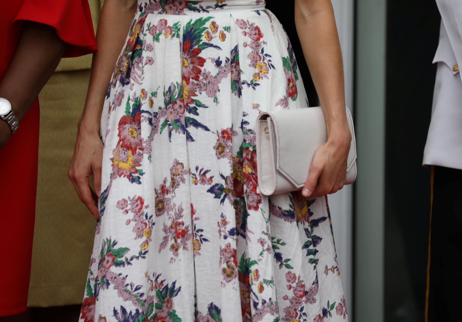 El detalle del estampado floral de su falda y de su clutch rectangular
