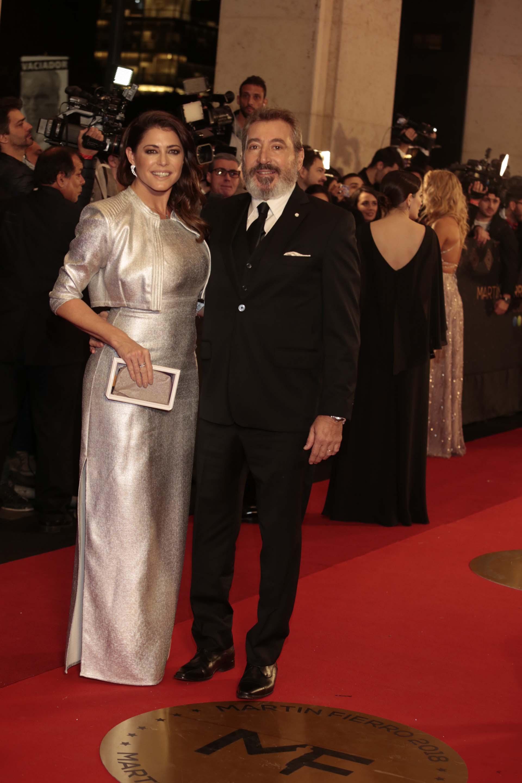 Pamela David con un vestido plateado y saco corto a tono, combinado con clutch blanco y gris acompañándolo con aros pequeños. Daniel Vila con traje negro, corbata y pochette en el bolsillo.