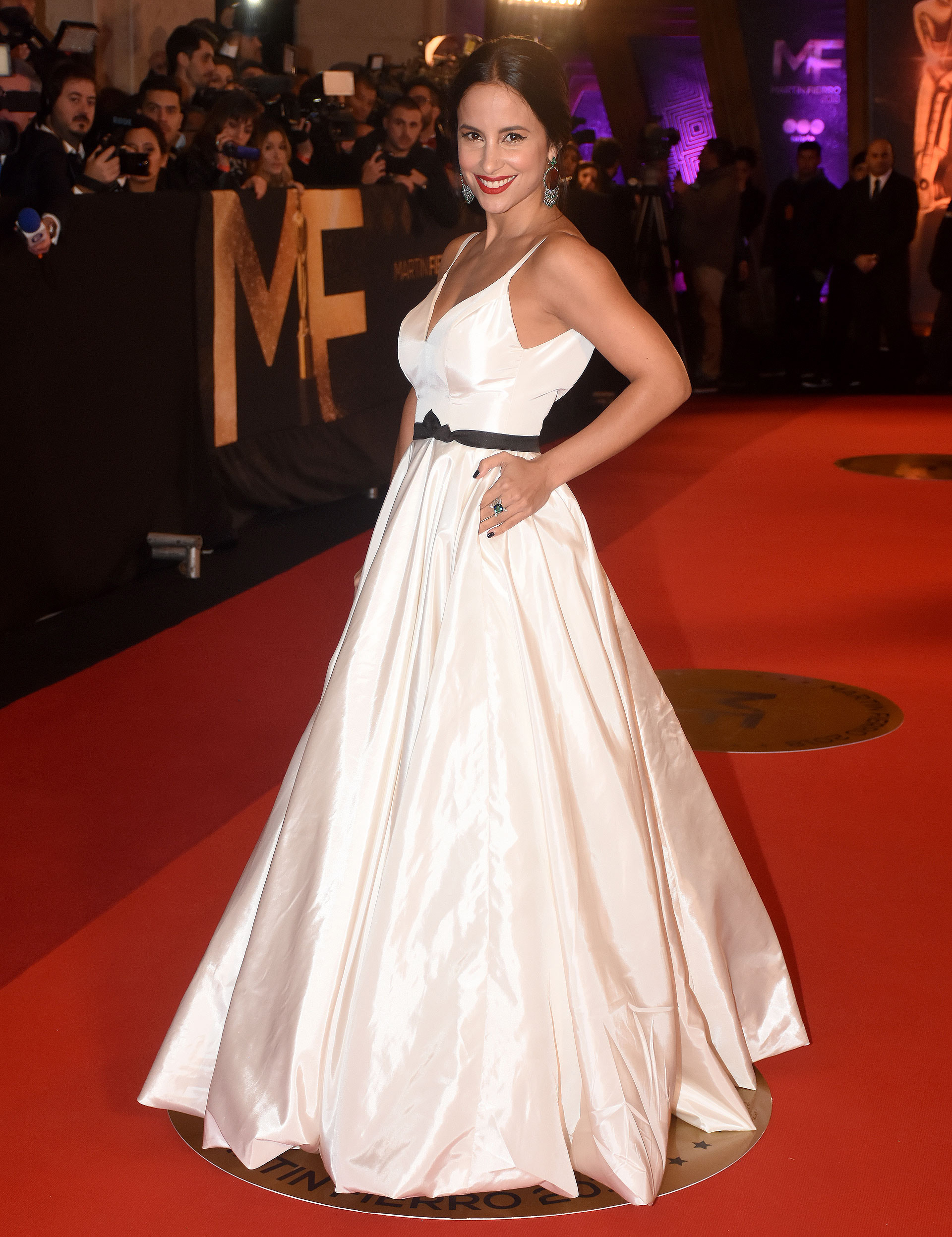 Lourdes Sánchez con un vestido princesa con detalle de cinta en la cintura. Acompañó el diseño con aros y anillo con esmeralda