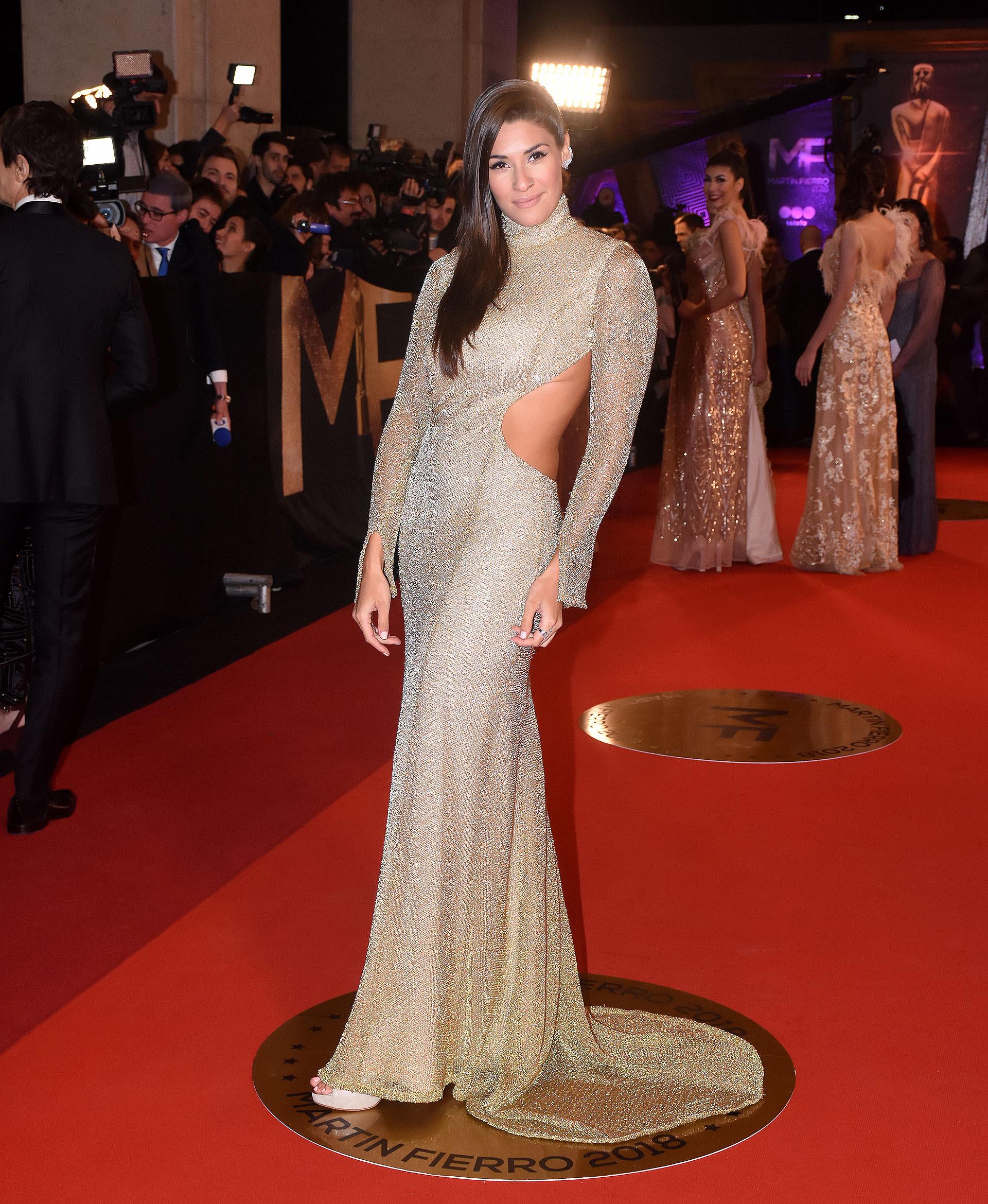 Ivana Nadal impactó con un vestido sirena con cola y gran escote en la espalda del diseñador Jota Cardozo en lúrex y corte cut out. Lo completó con stilettos con boca de pez y anillos.
