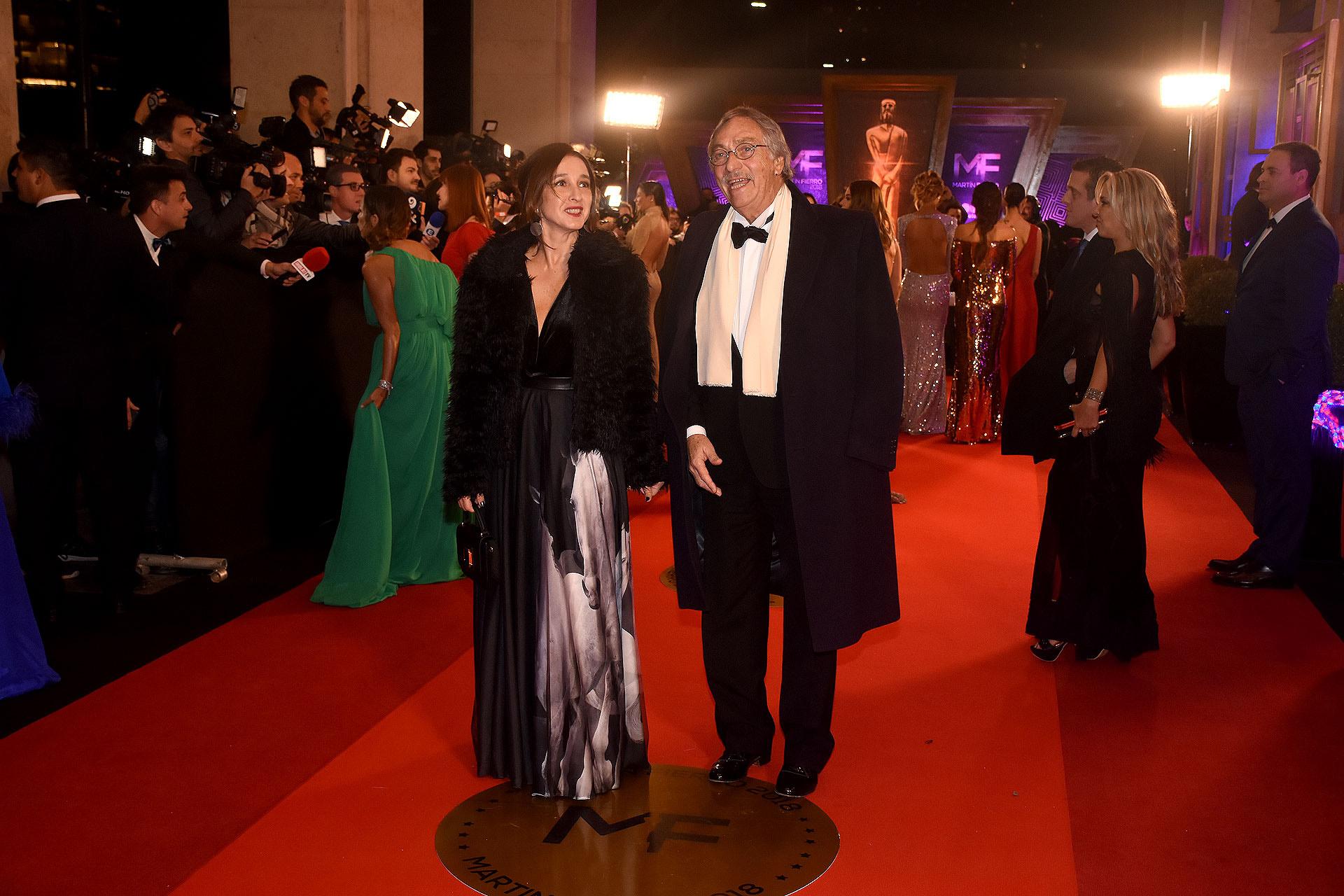 Luis Brandoni con traje negro, camisa blanca y moño negro. Lo combinó con una chalina beige y sobretodo a tono. Su mujer lo acompañó con un vestido estampado en blanco, negro y gris.