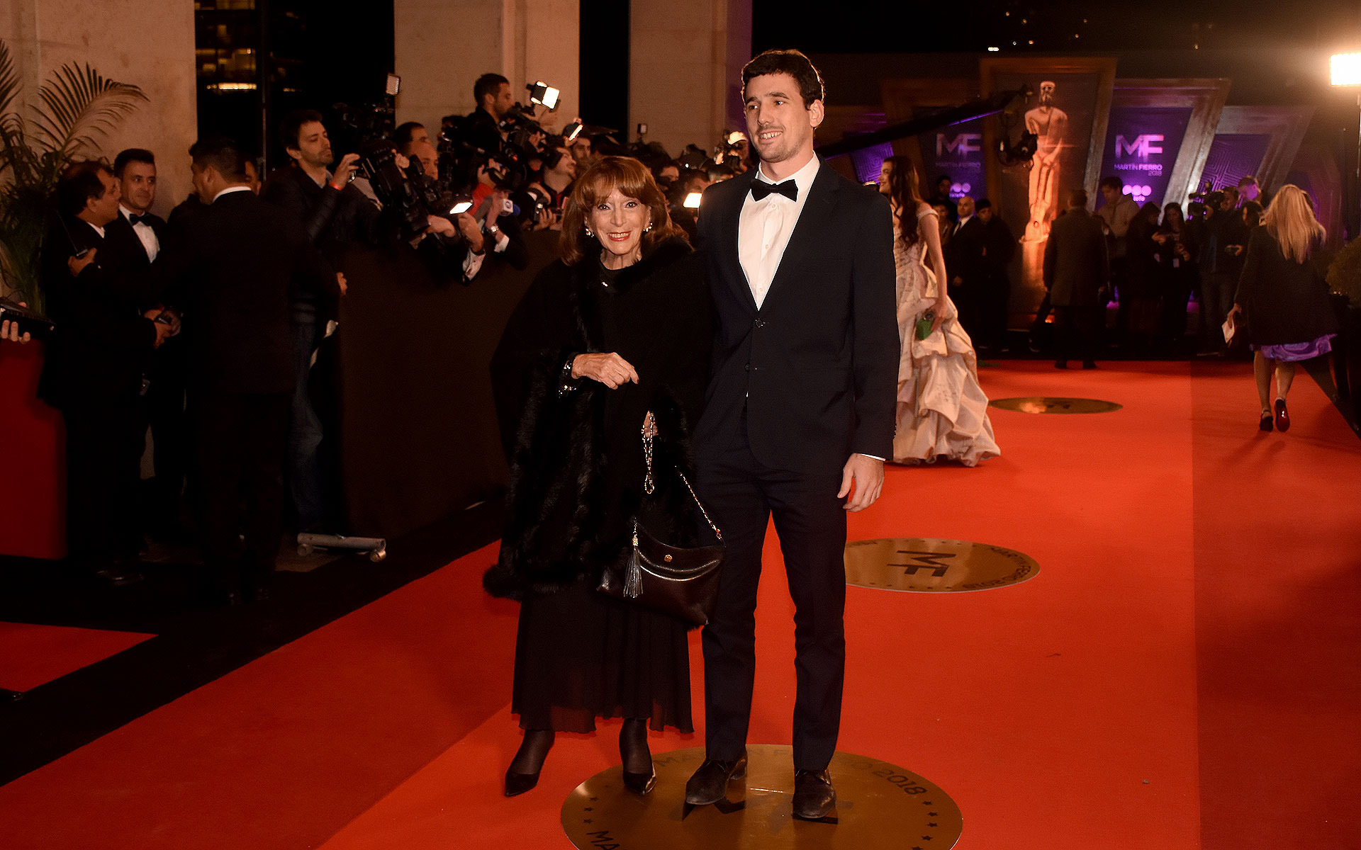 Magdalena Ruiz Guiñazú con un look total black con tapado, cartera negra y stilettos en punta de gamuza.