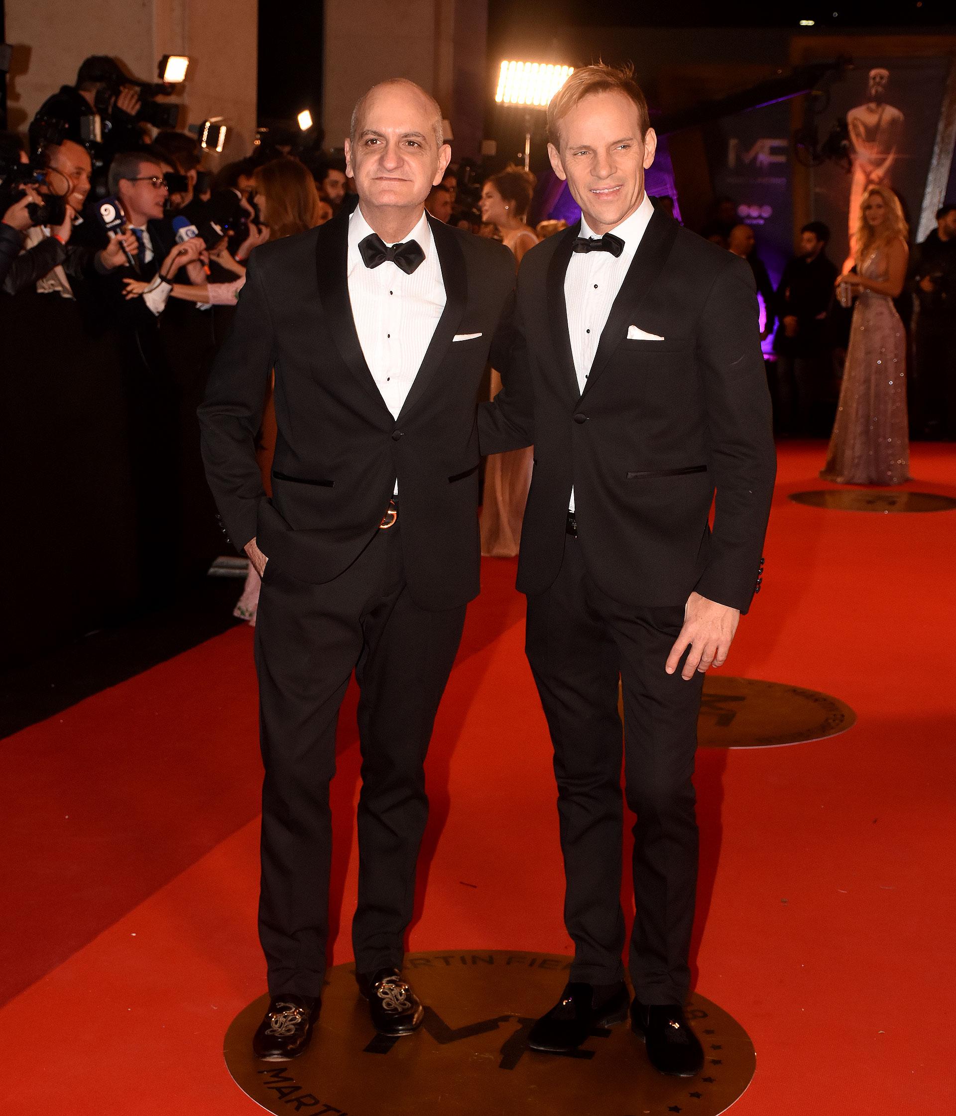 Laurencio Adot y Thiago Pinheiro, ambos en black tie con mocasines y pochette blanco.