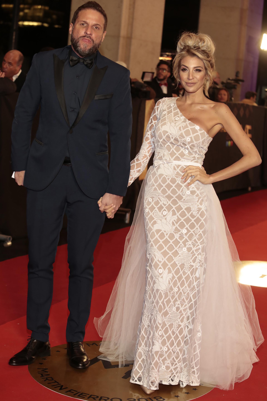 Stefy Xipolitakis junto a su marido Sebastián Pelish. Ella eligió un diseño al cuerpo de un solo hombro con sobrefalda de tul. Él, un smoking azul con detalles en negro.