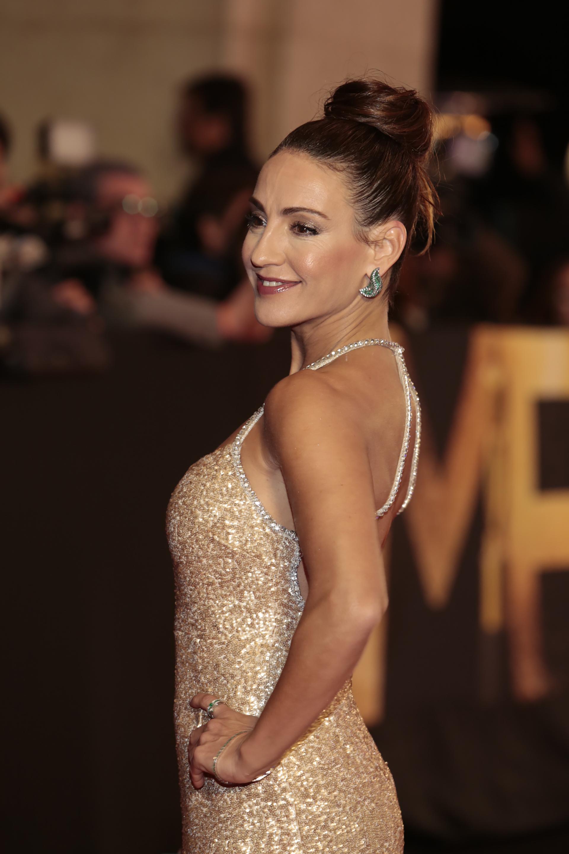Eleonora Wexler con vestido sirena de pailletes en dorado con espalda al descubierto y aros joya con detalles de piedra verde