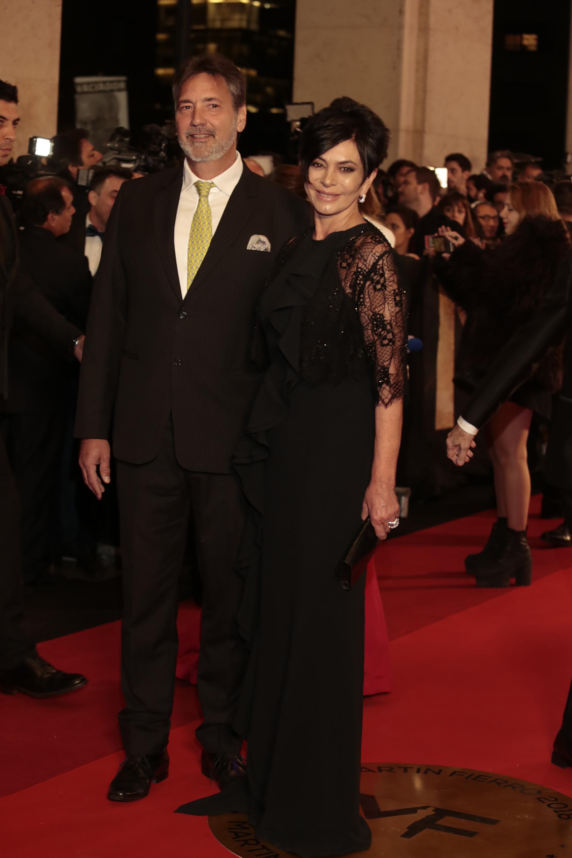 Mónica Gutiérrez y su marido. Ella eligió un diseño de Menage a Trois en negro con mangas de encaje y jabot a lo largo de todo el vestido. Él la acompañó con un traje clásico con corbata en color verde manzana.
